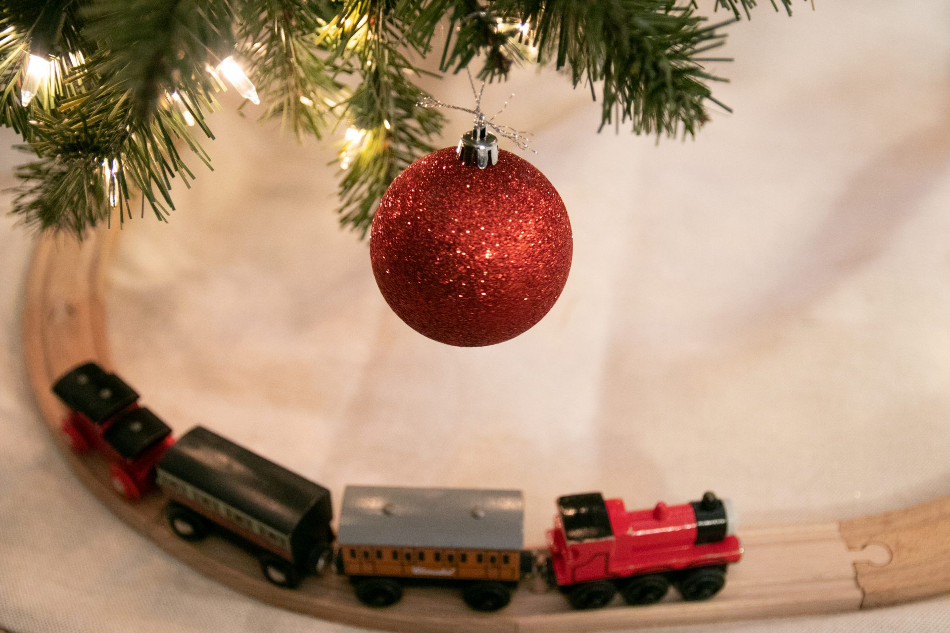 Toy Train On Tracks Below Hanging Red Bauble Ornament