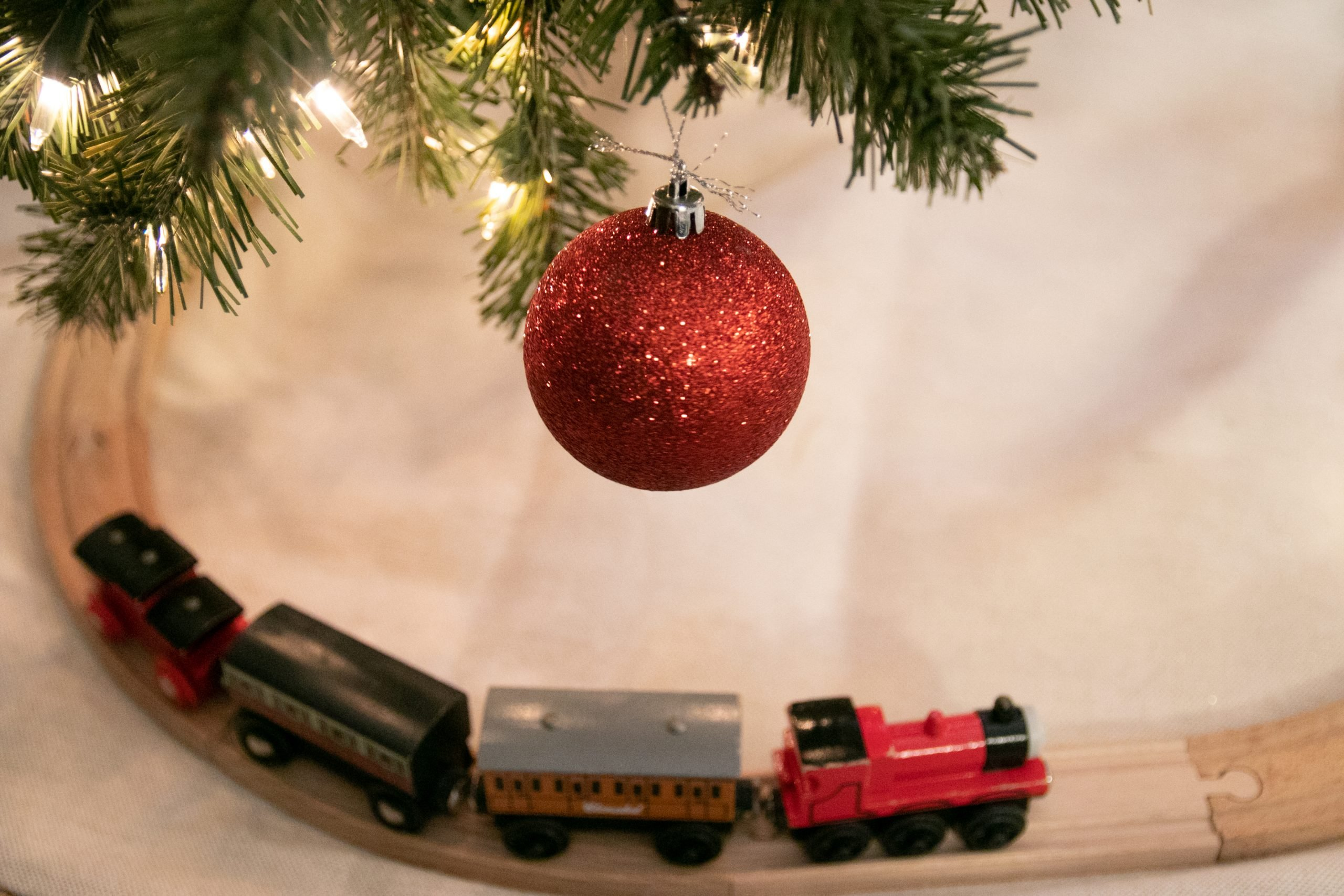 Free Stock Photo of Toy Train On Tracks Below Hanging Red Bauble Ornament