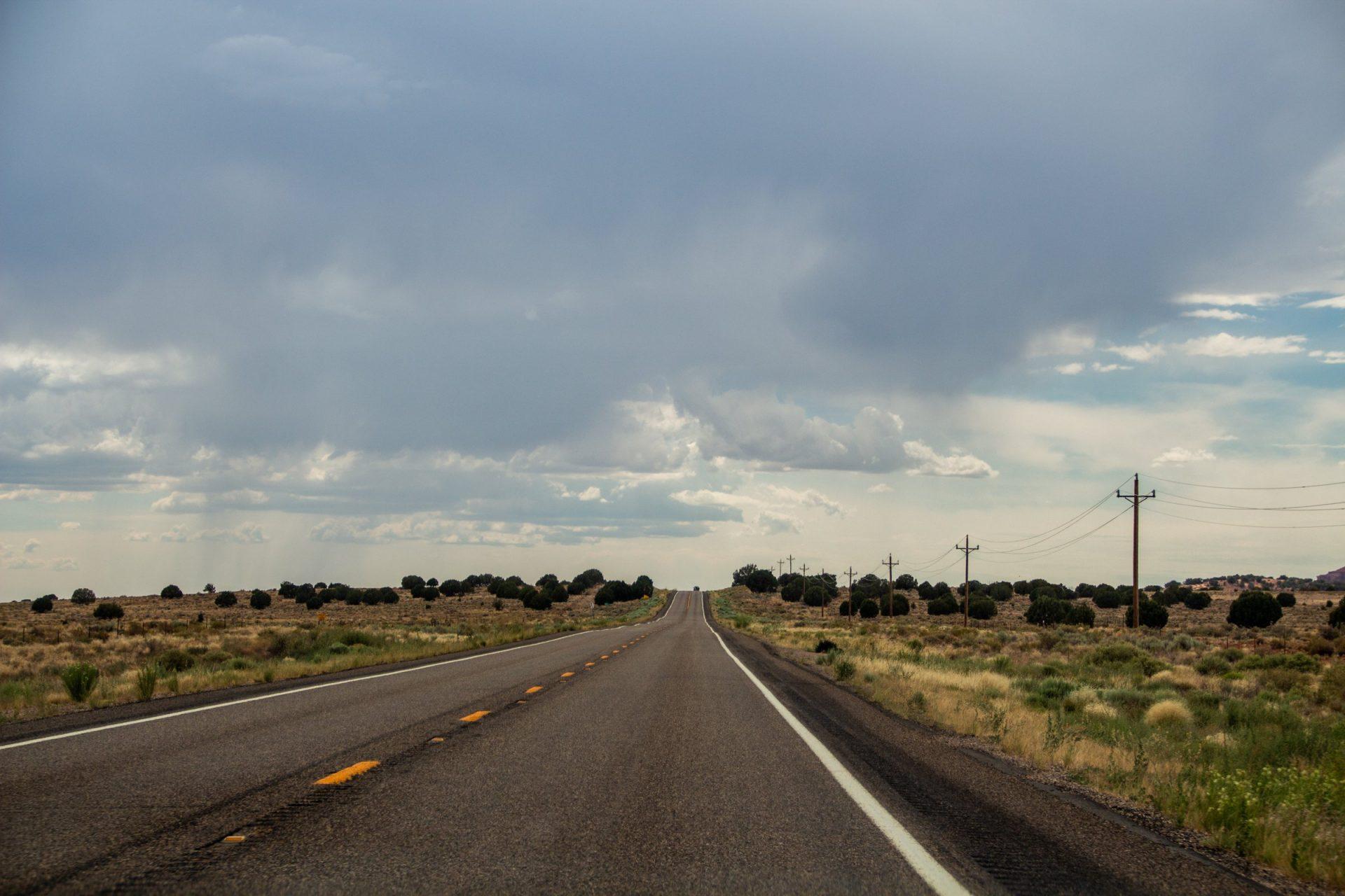 Empty Desert Road Under Cloudy Sky