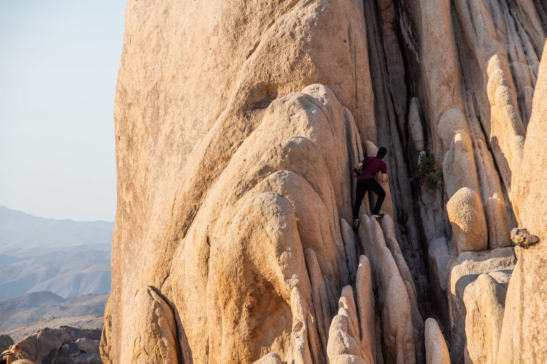 Man Climbing Rock Formation In Joshua Tree Park