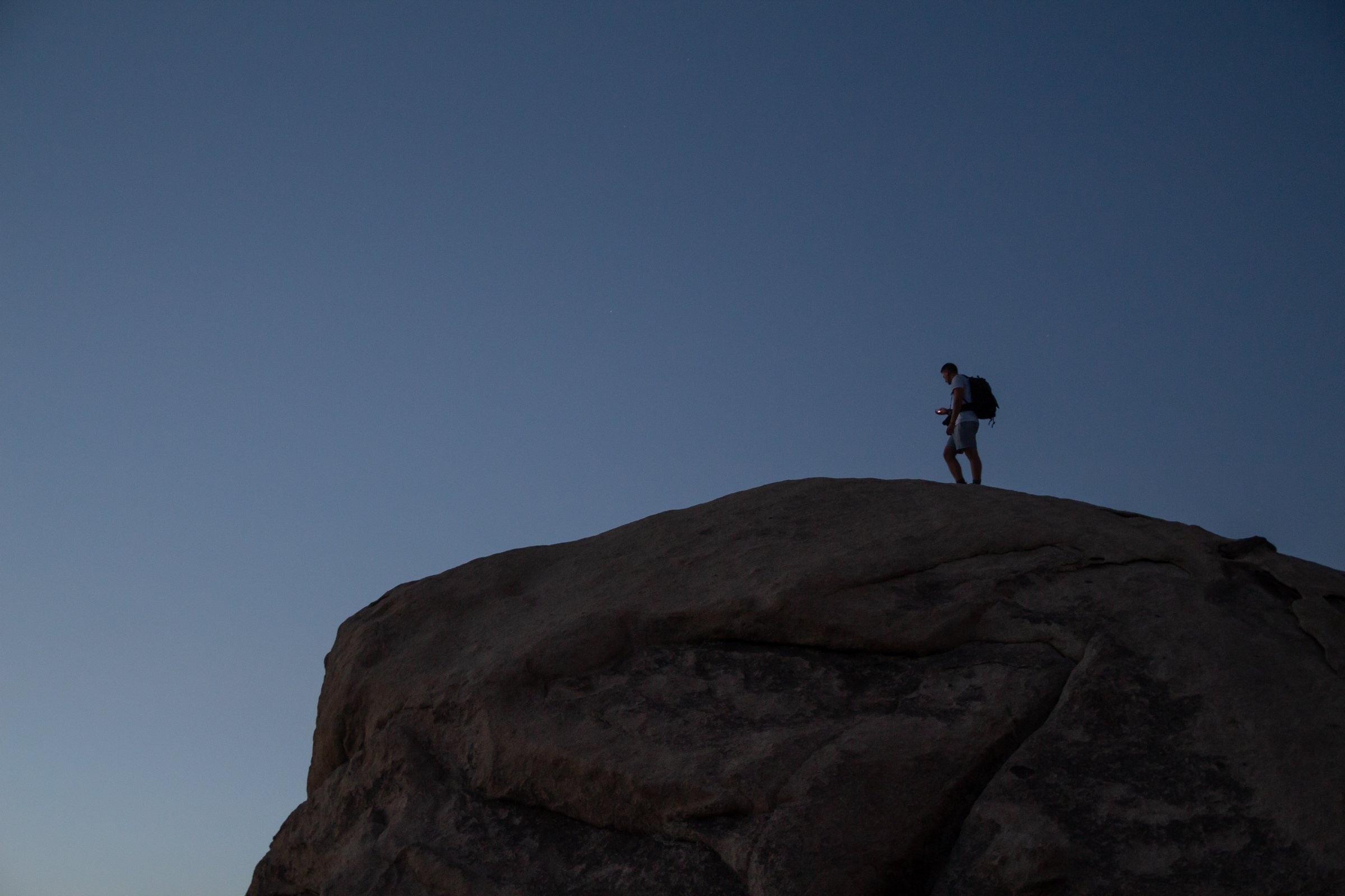 Man With Backpack On Rock In Joshua Tree Park