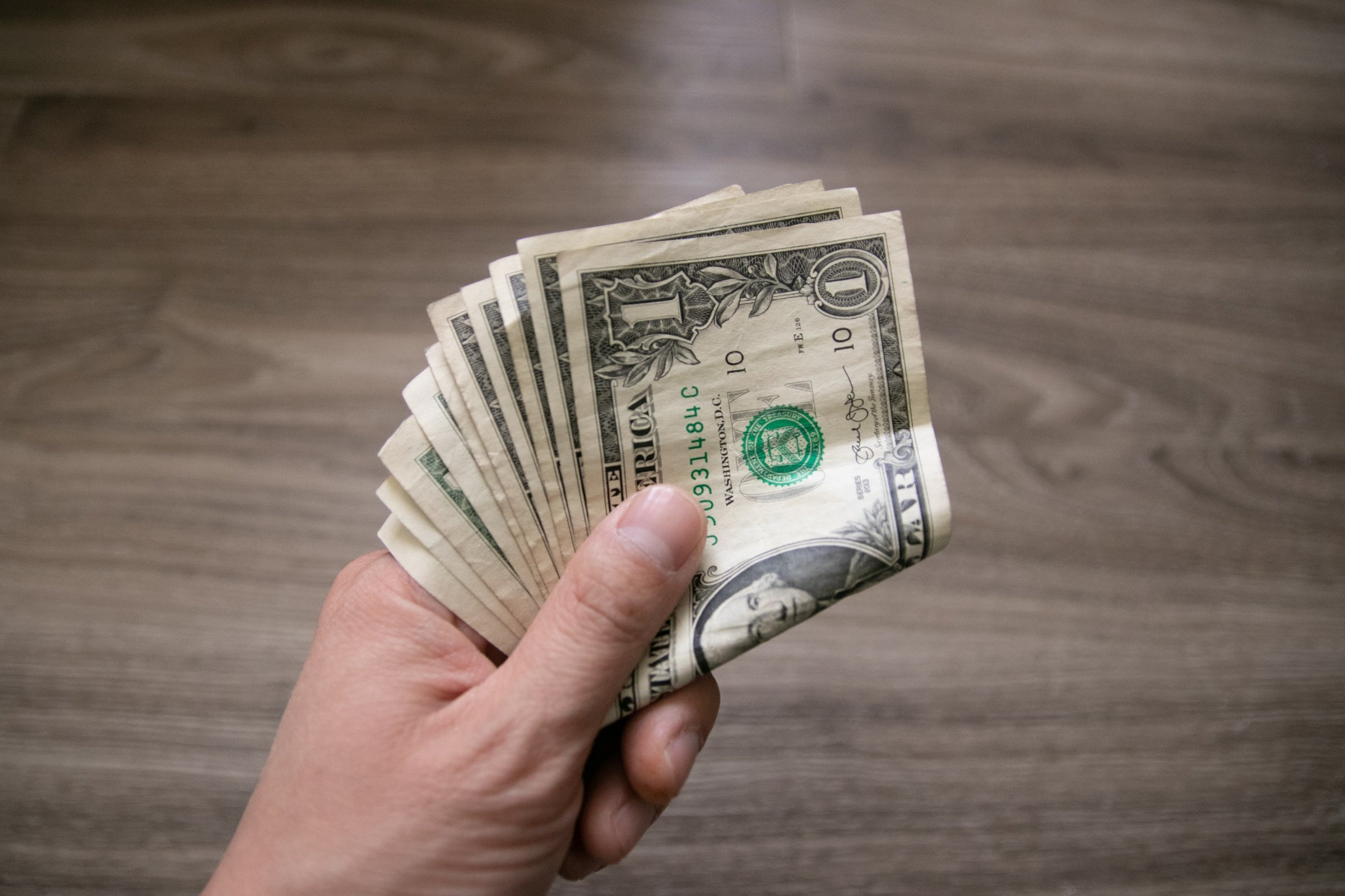 One Dollar Bills In Left Hand