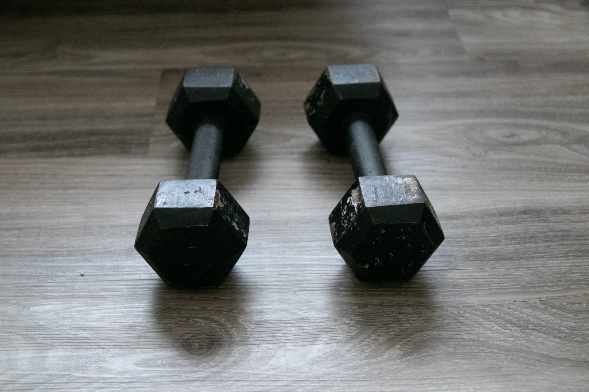 Pair Of Black Dumbbells On Wooden Surface