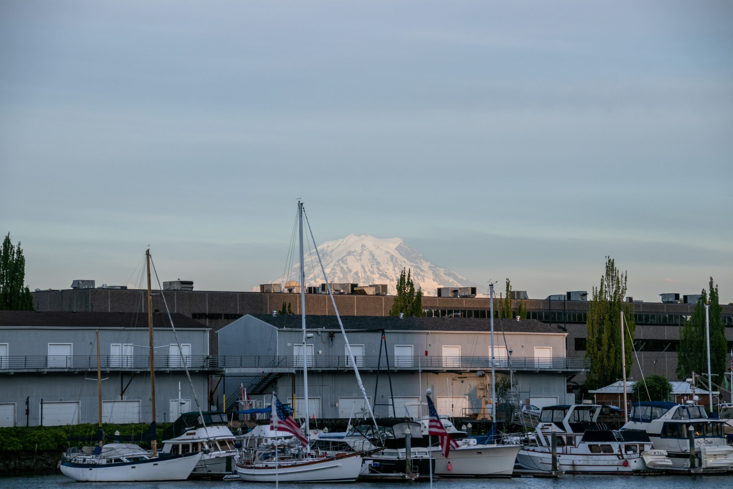 Snow Capped Mountain Behind Boats In Harbor