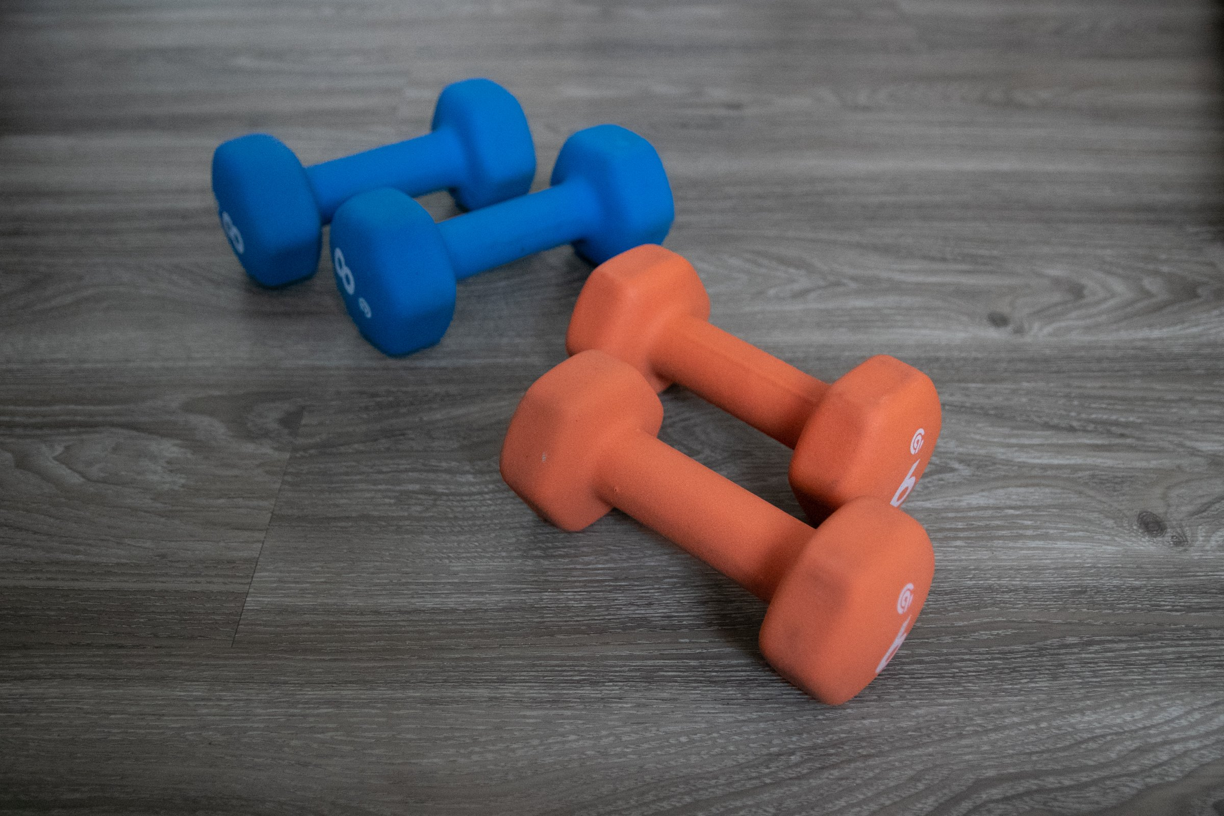 Two Pairs Of Dumbbells On Wooden Surface