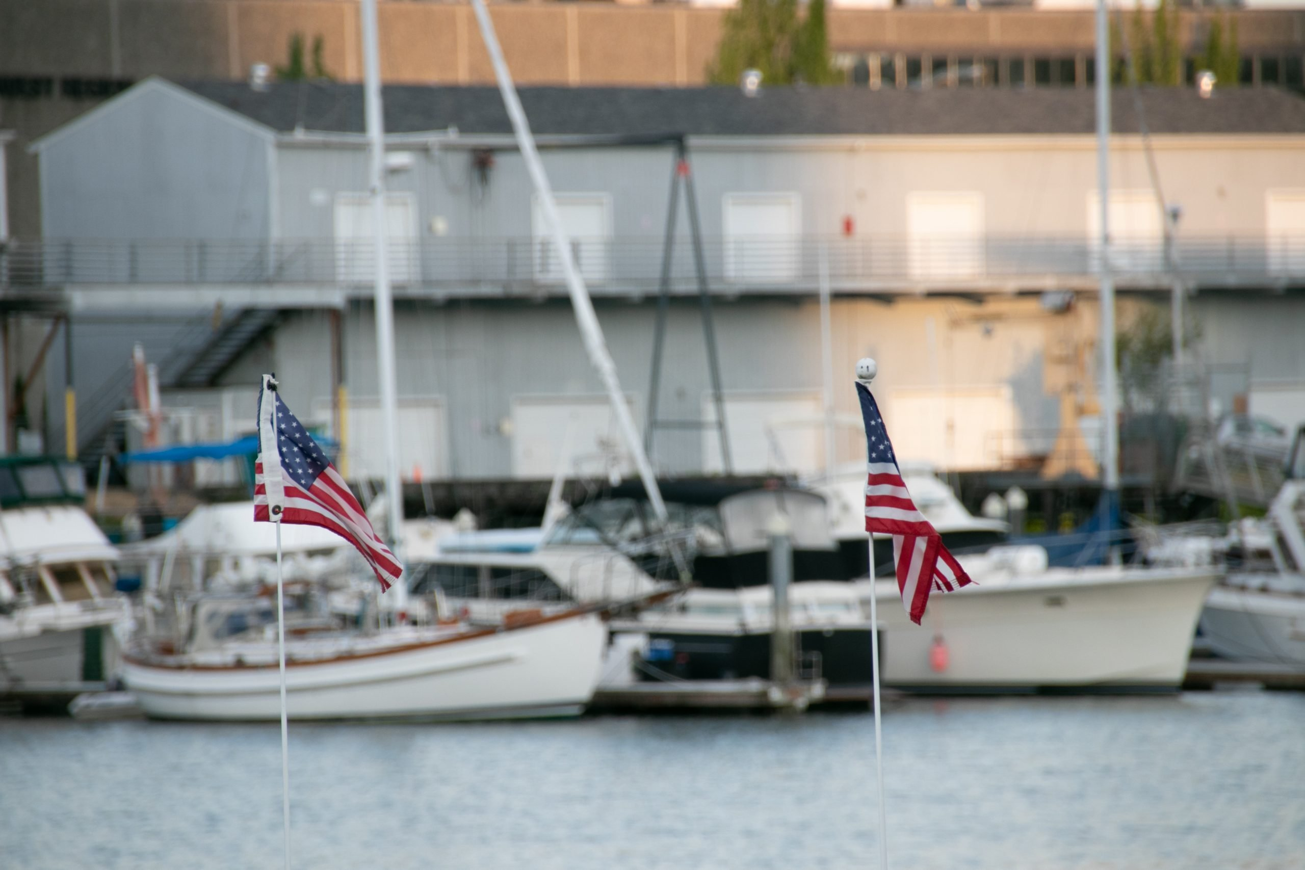Two Small American Flags Near Docked Boats