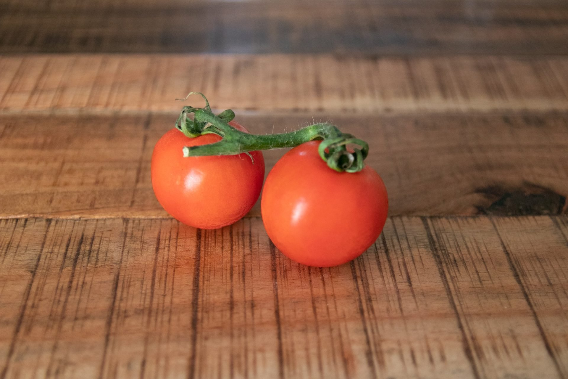 Two Tomatoes On Wooden Surface