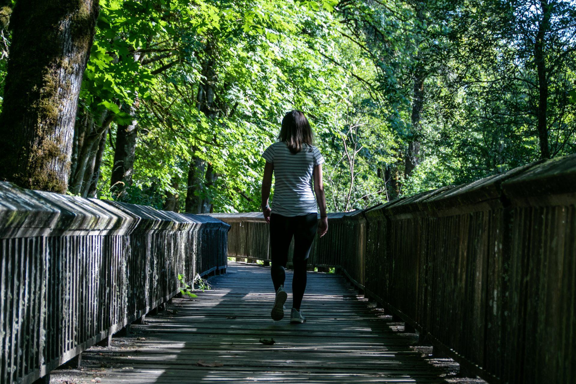 Woman Walking Down Wooden Boardwalk Between Trees