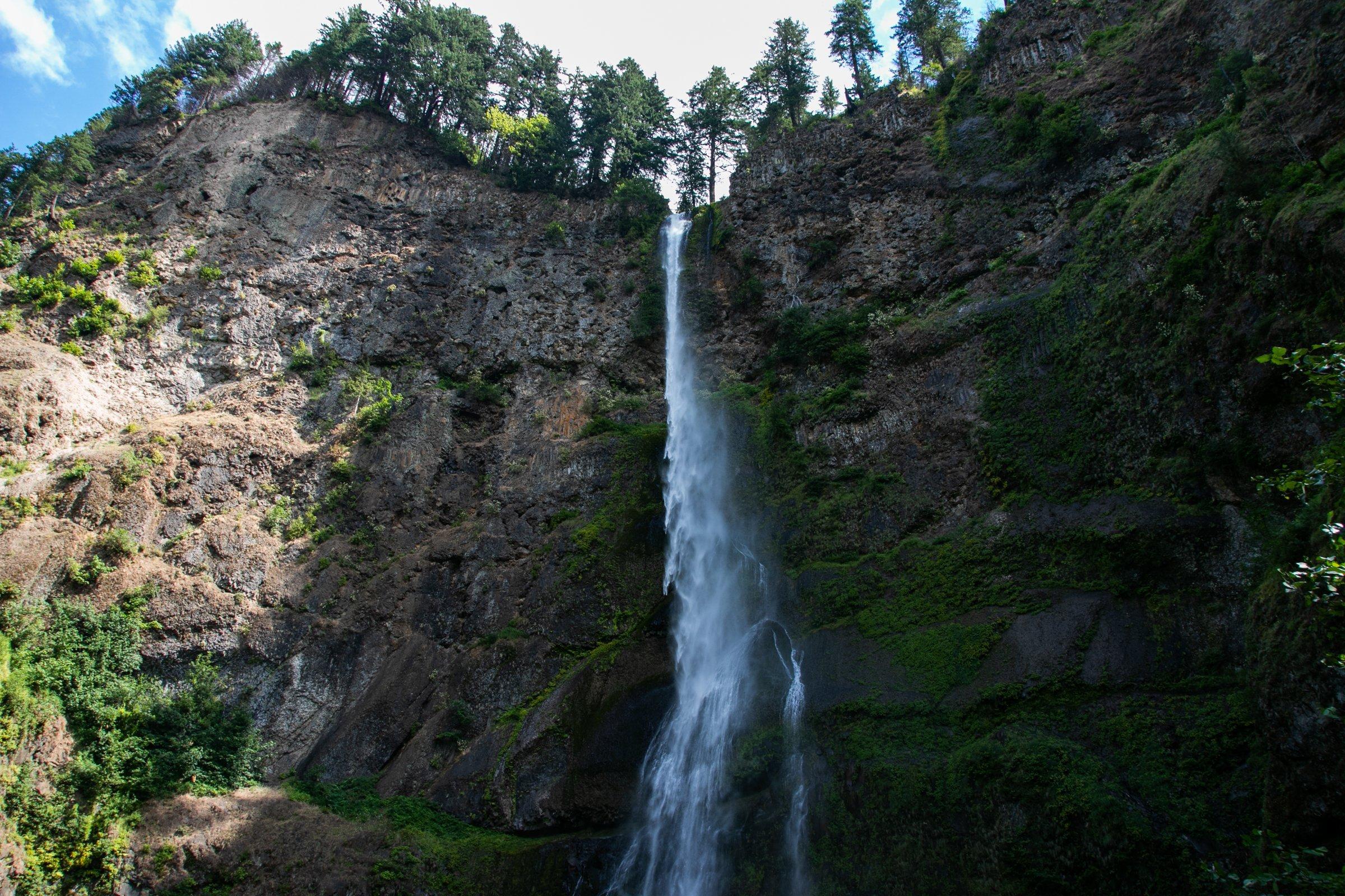 Long Narrow Waterfall On Mountain Cliff