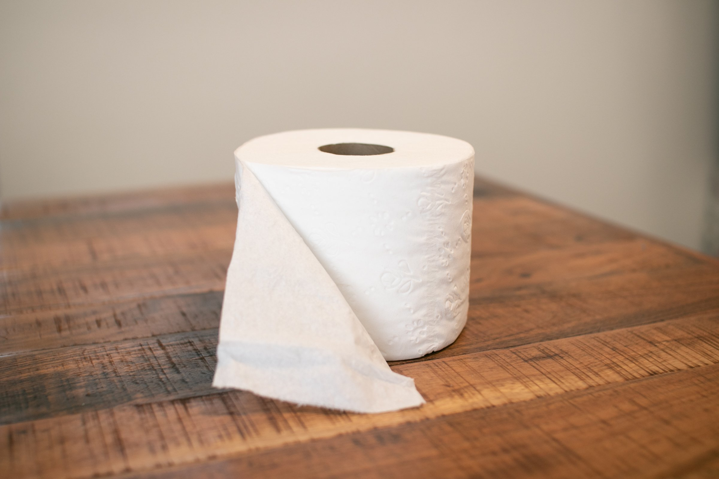 Open Toilet Paper Roll On Wooden Surface