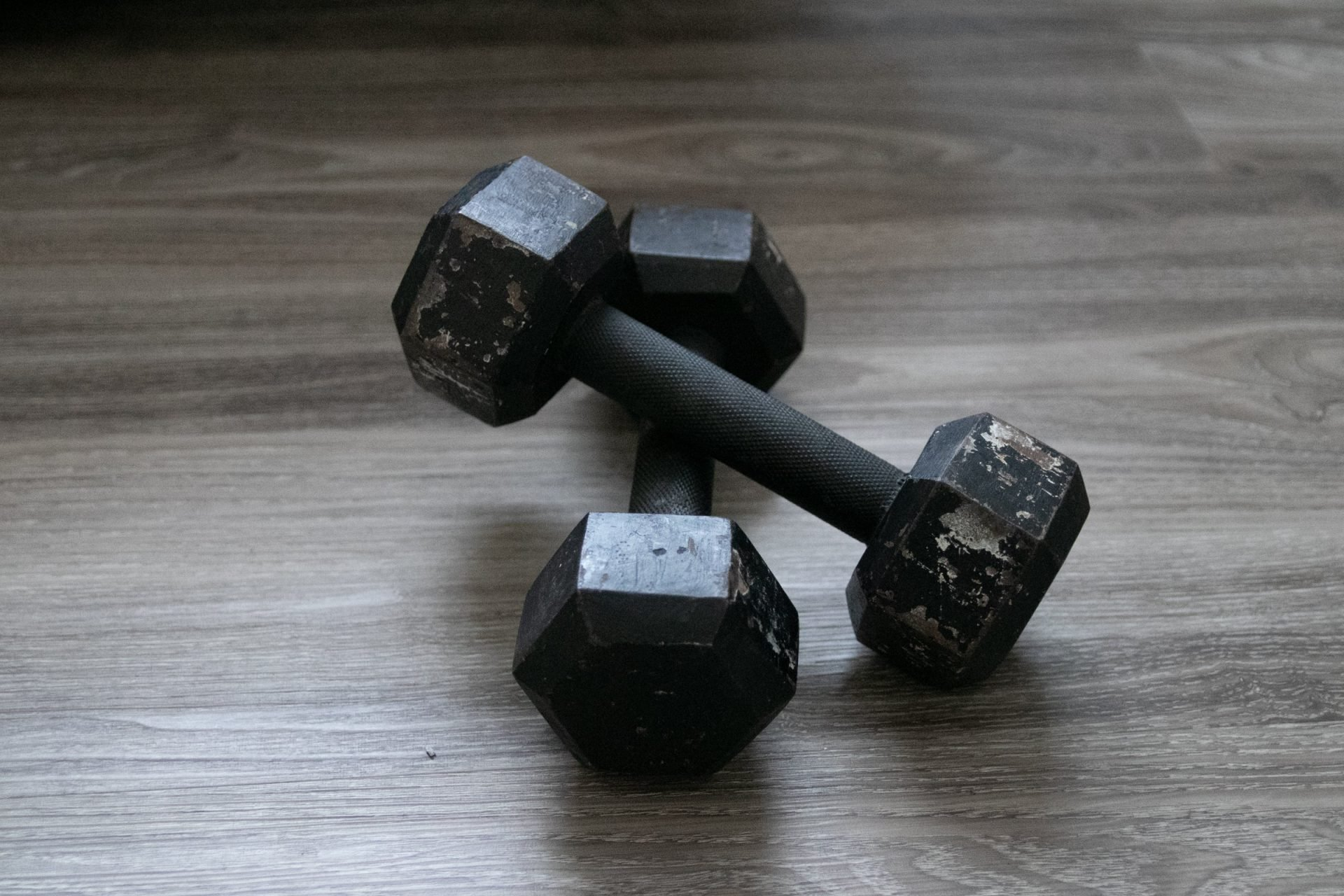Pair Of Scratched Black Dumbbells On Wooden Surface