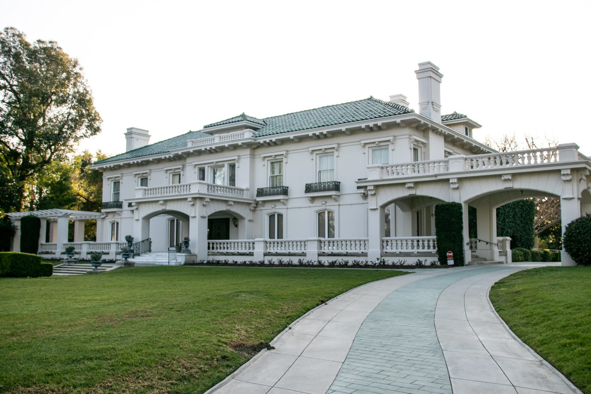 Side Walkway Leading To Large White Mansion