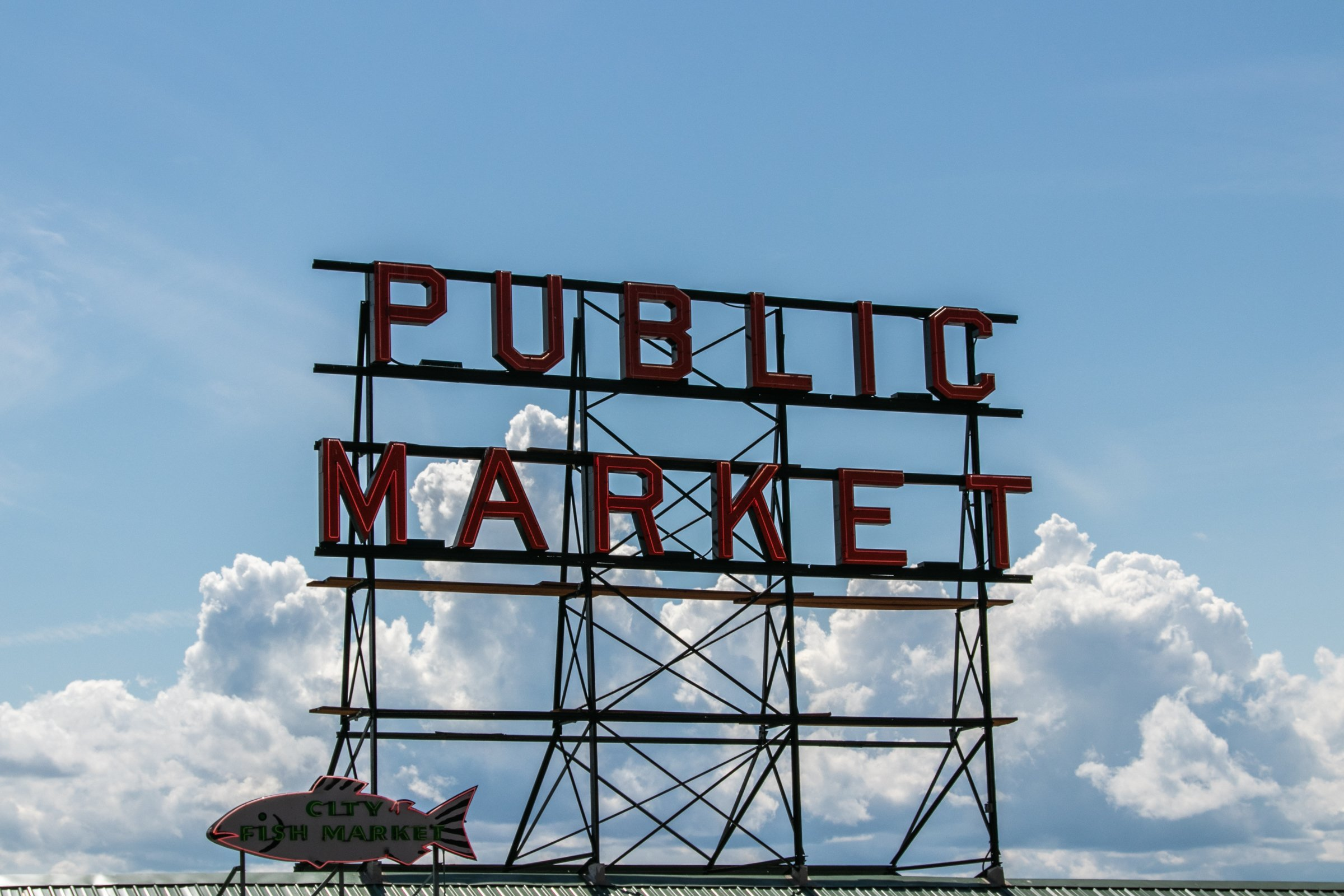 Unlit Public Market Neon Sign Against Clouds