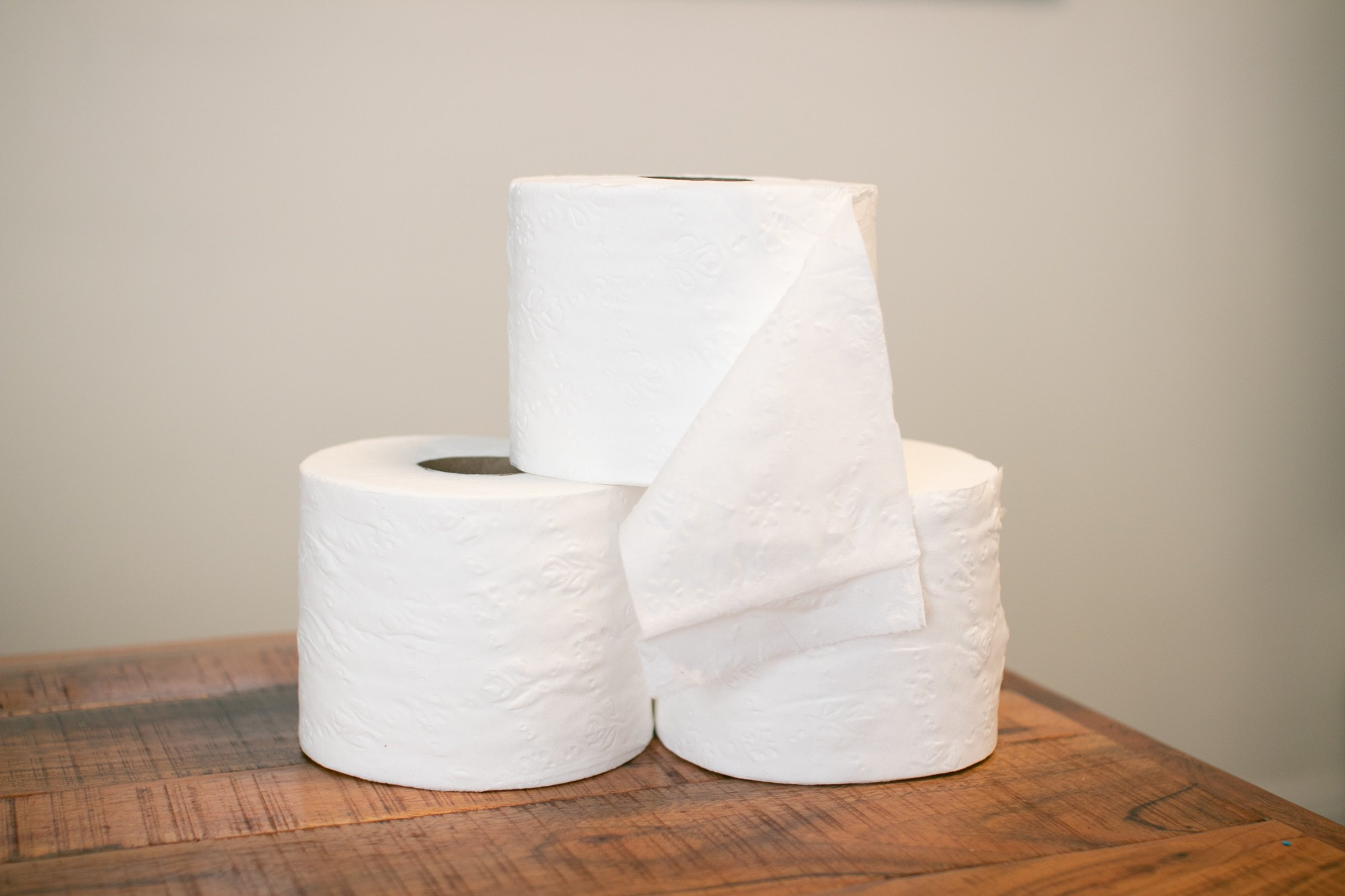 Three Stacked Toilet Paper Rolls On Wooden Table