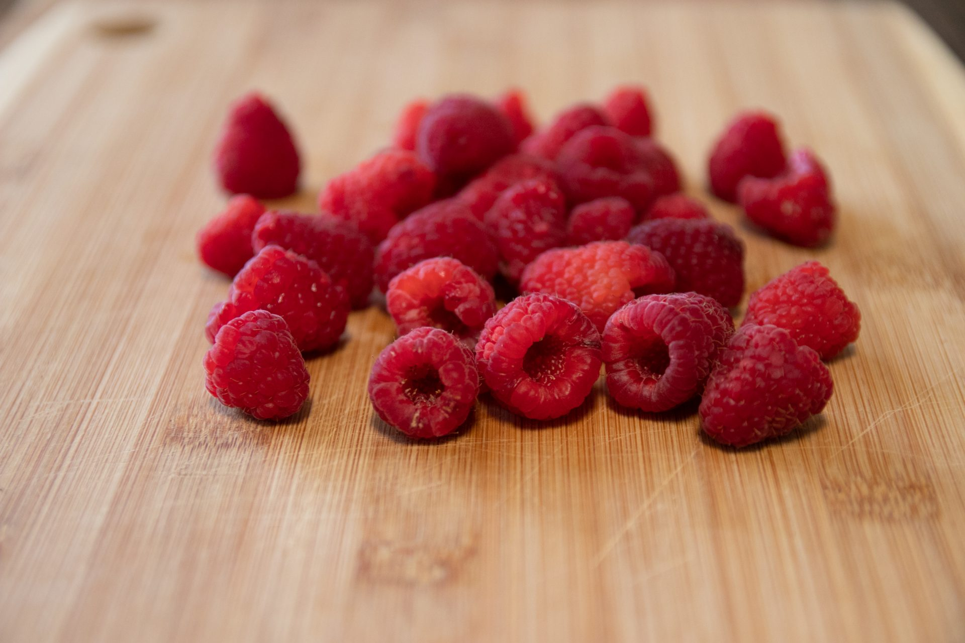 Close Up Of Raspberries On Wooden Cutting Board