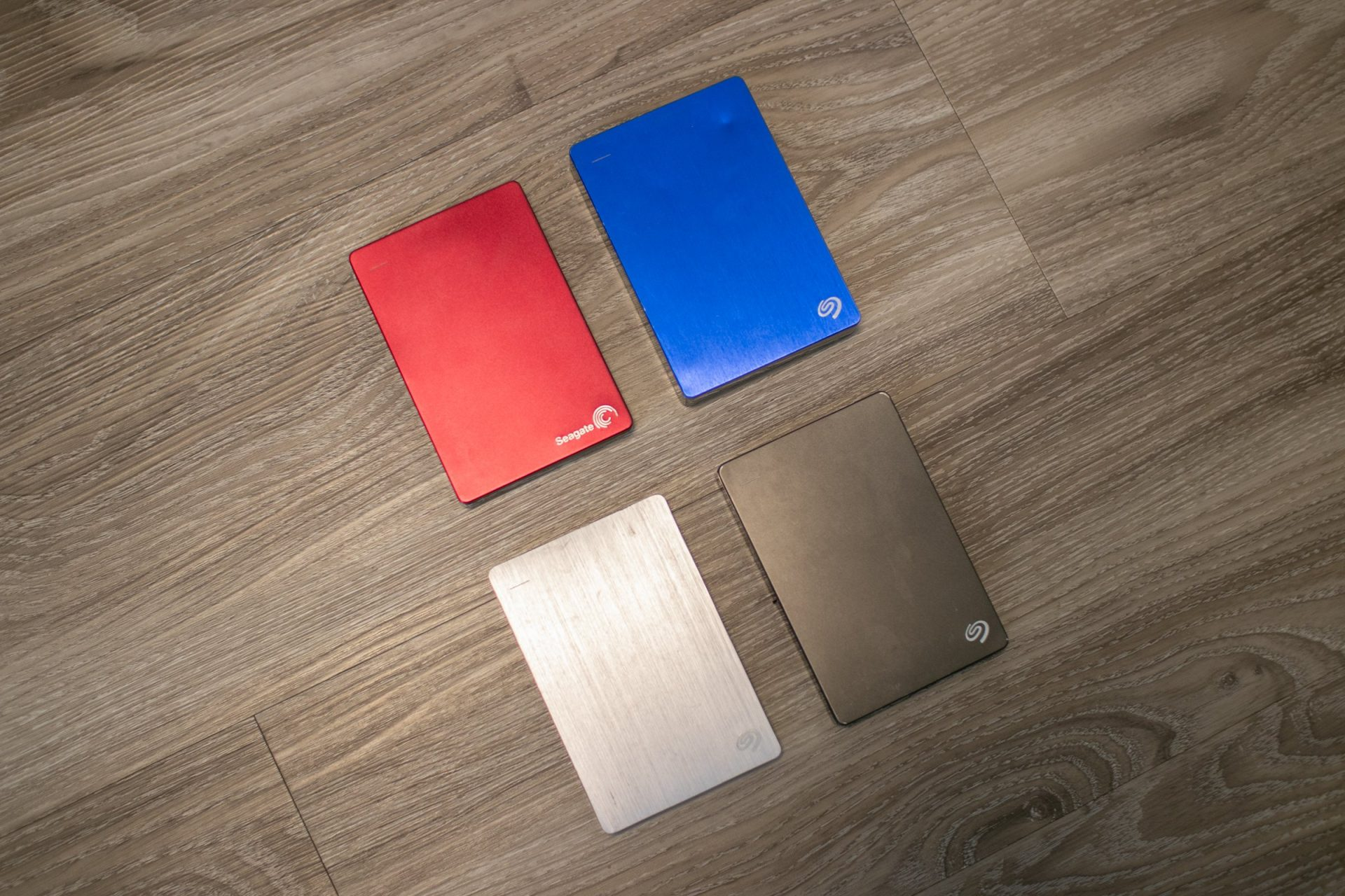 Four External Hard Drives On Wooden Surface