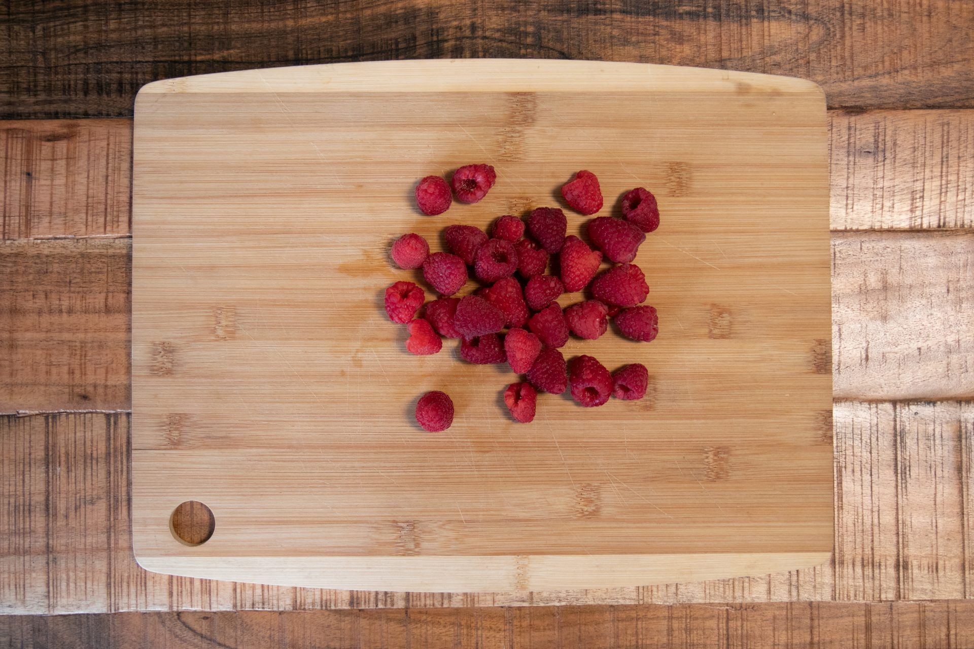 Handful Of Raspberries On Wooden Cutting Board