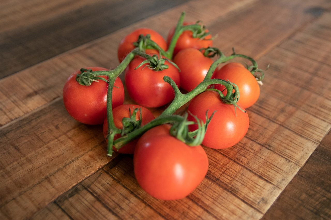 Handful Of Small Tomatoes On Wooden Surface