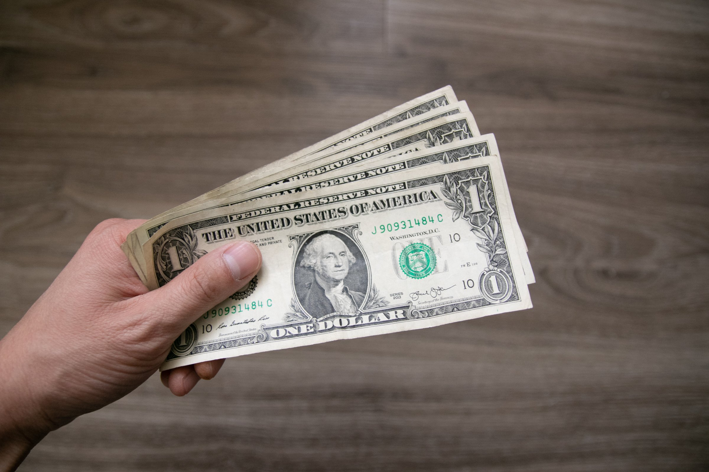 Left Hand Holding One Dollar Bills
