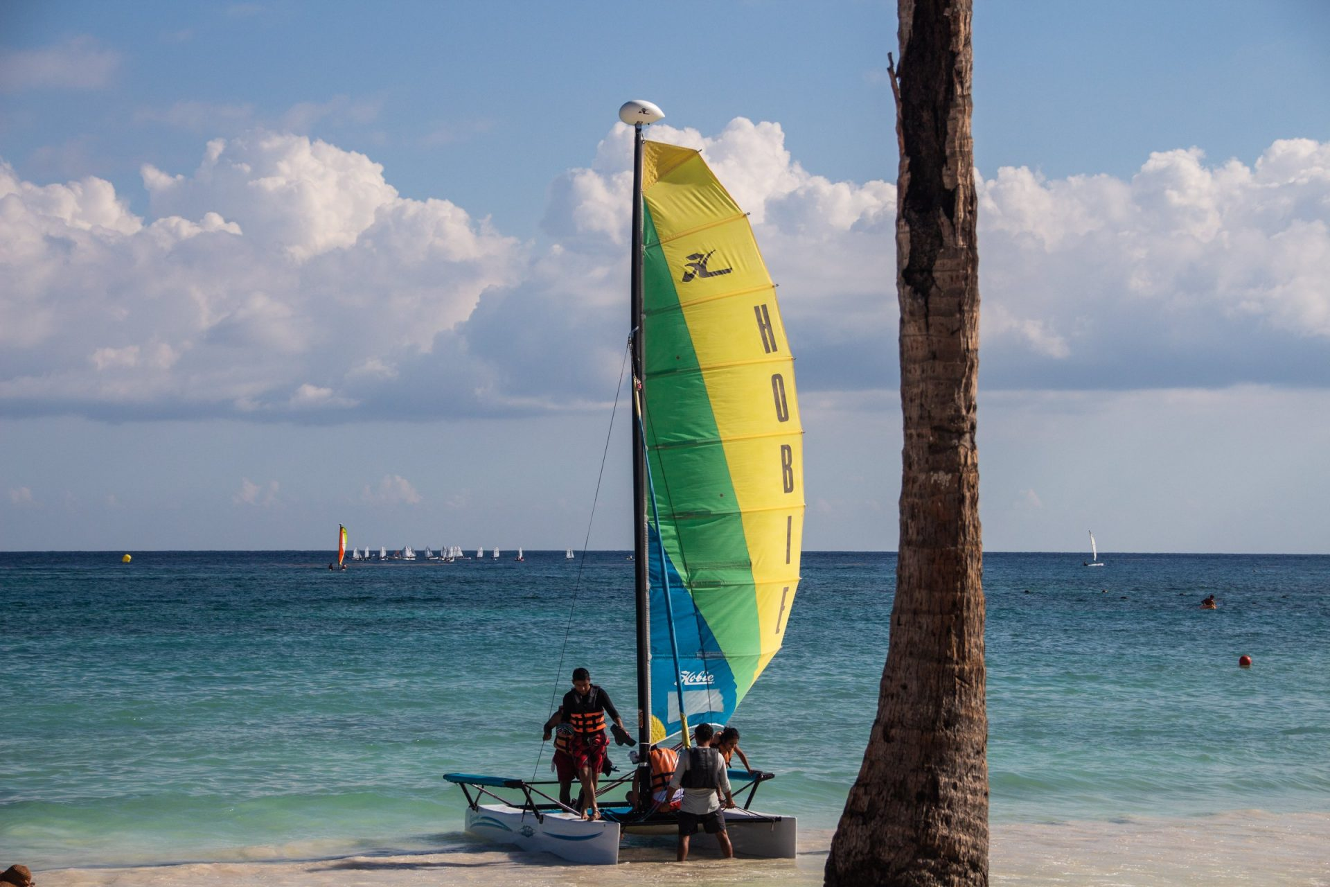 People On Catamaran Sailboat On Sandy Shore