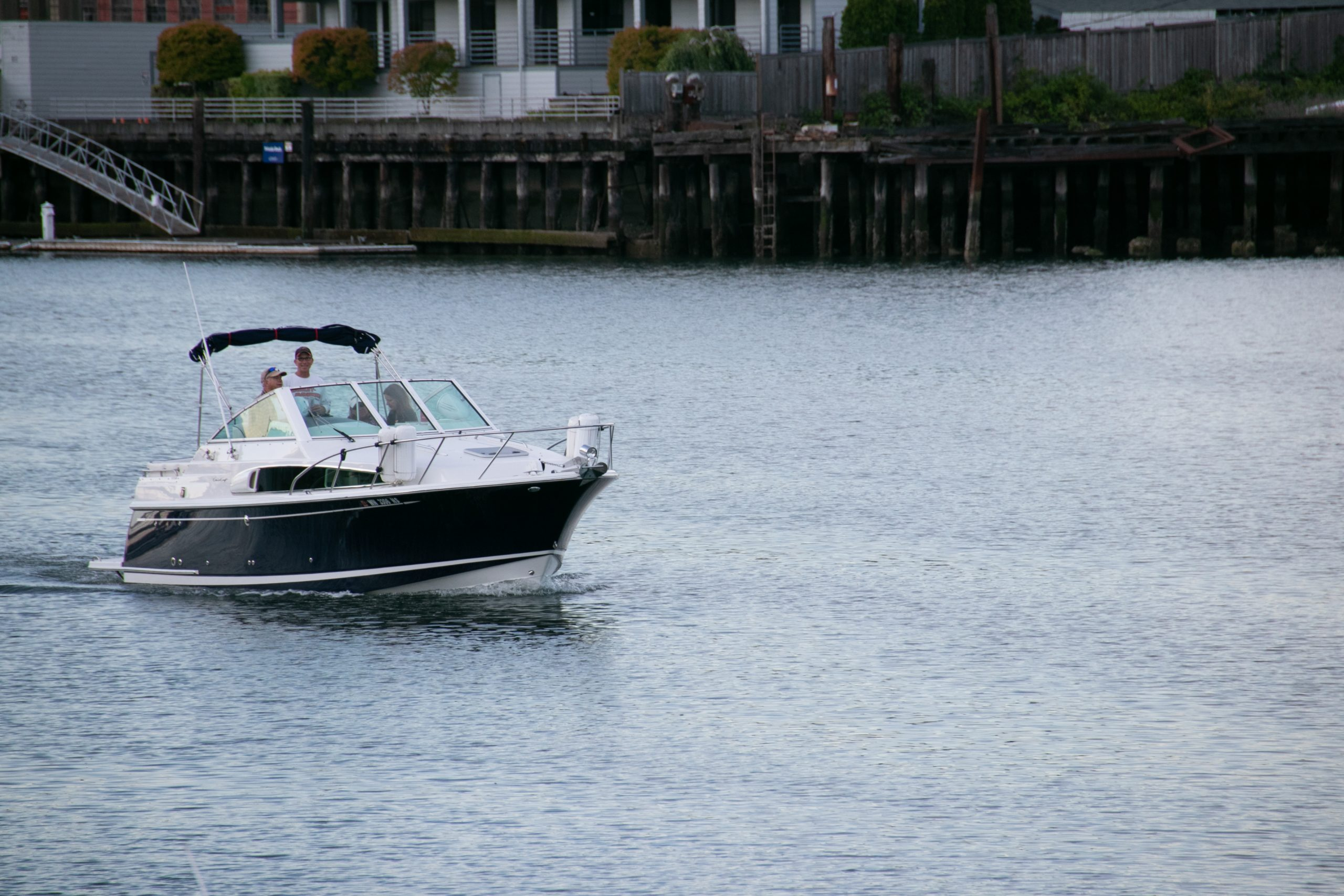 People On Motorboat On Water Near Shore