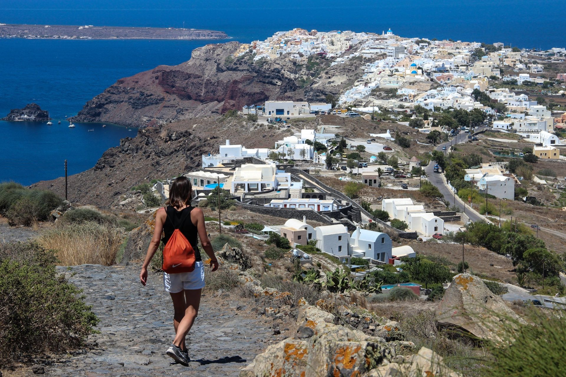 Person Walking Down Towards Town In Santorini Island