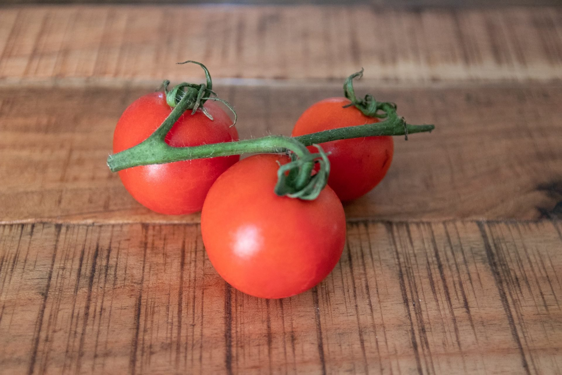 Three Tomatoes On Wooden Surface