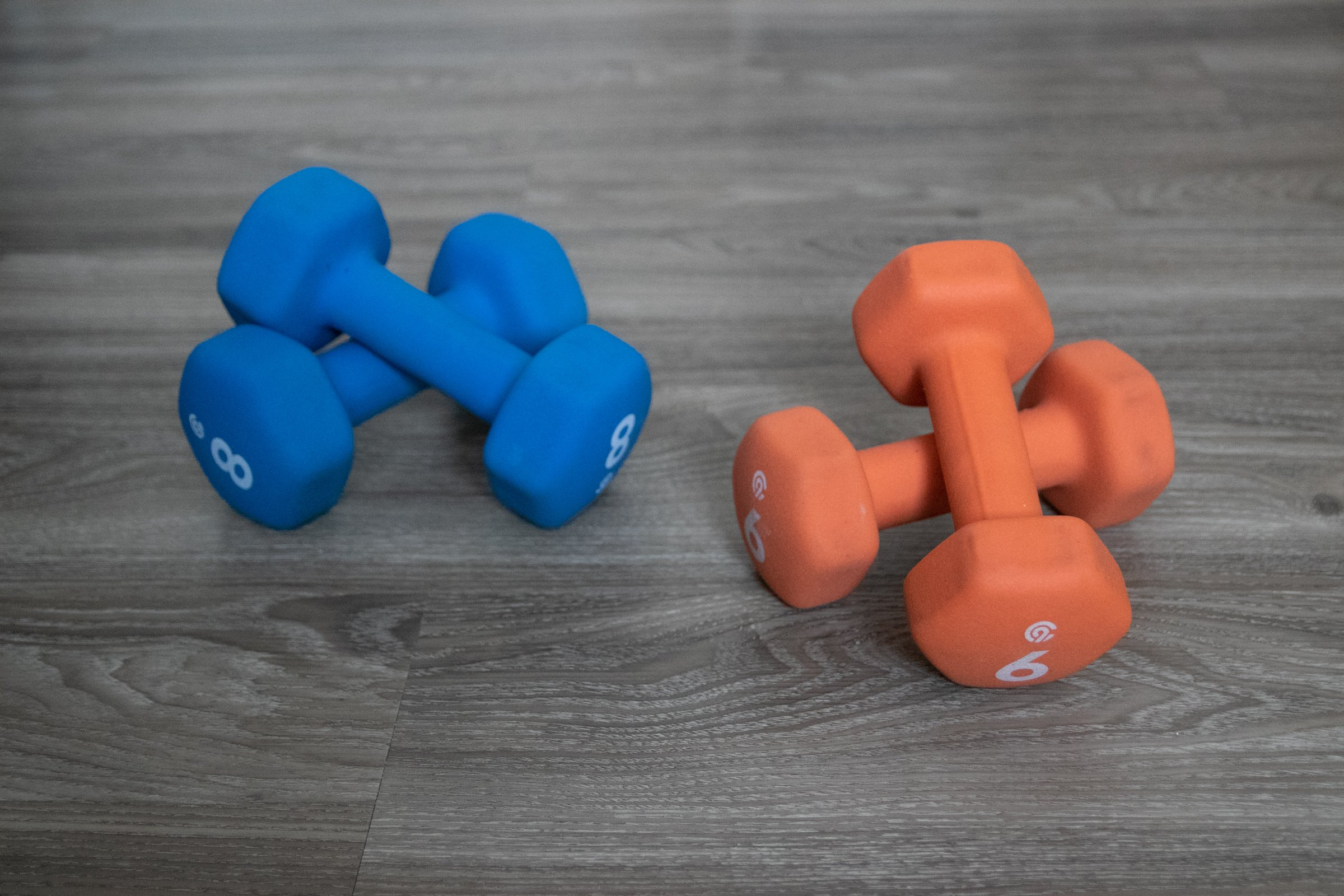 Two Sets Of Brightly Colored Dumbbells On Wooden Surface