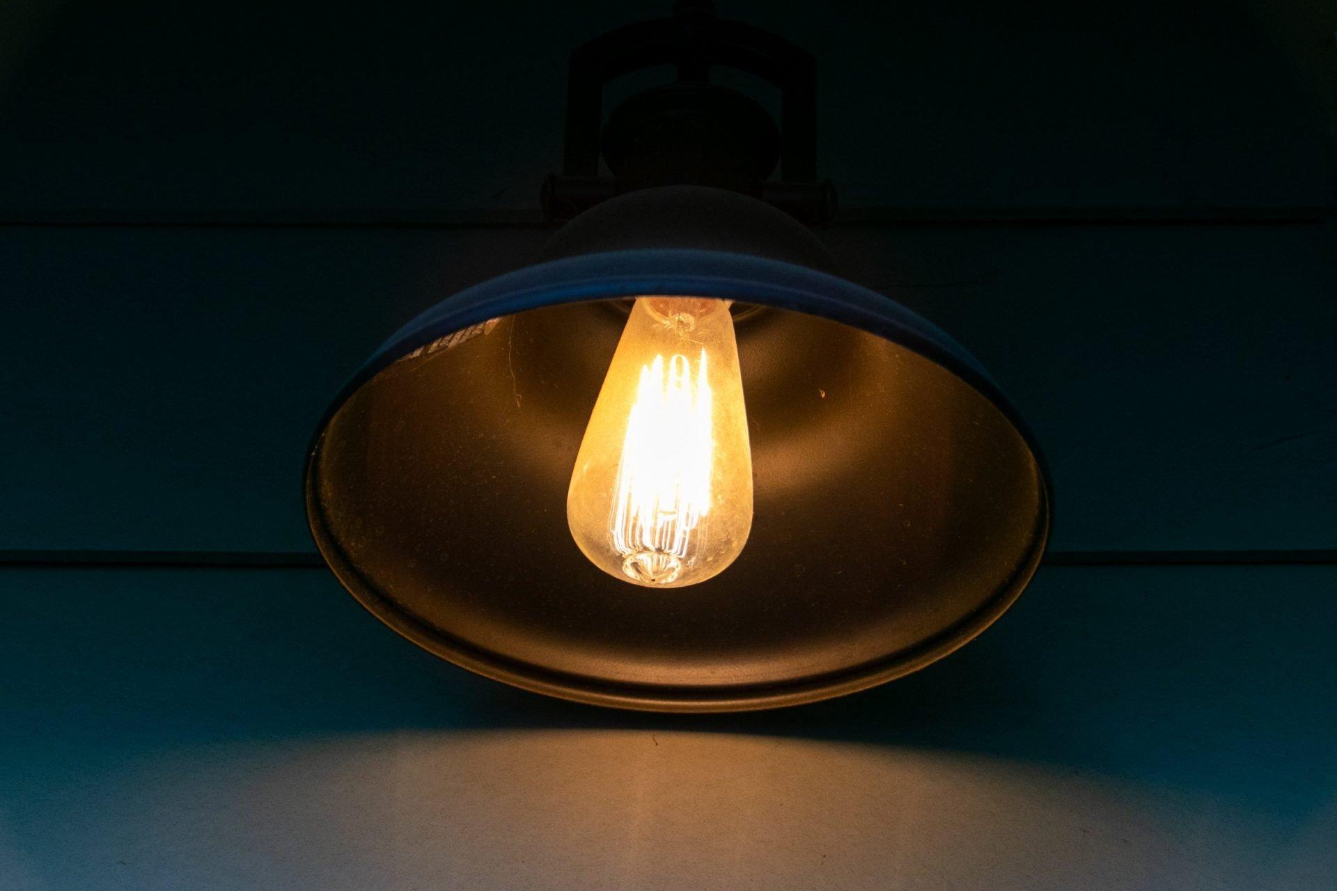 Lit Light Bulb In Wall Sconce