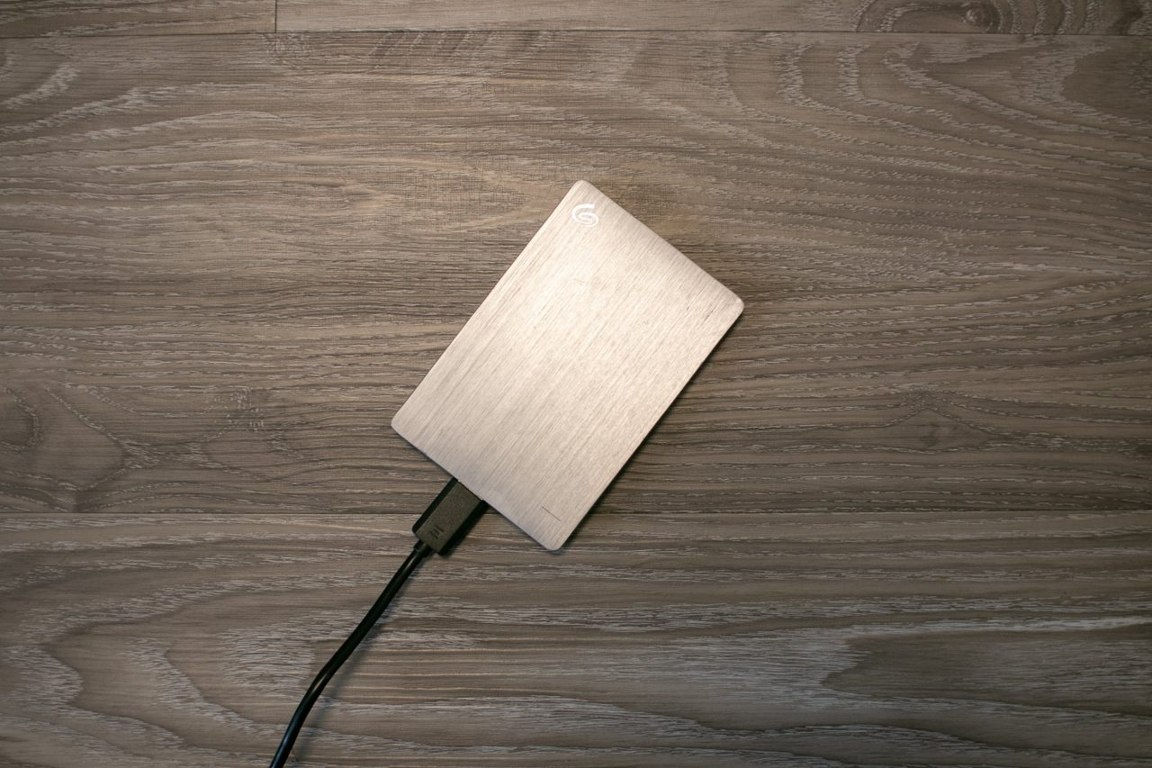 Plugged Silver External Hard Drive On Wooden Surface