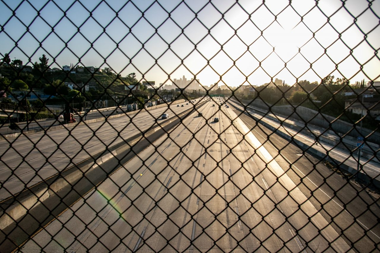 Sun Beyond Highway Behind Chain Link Fence