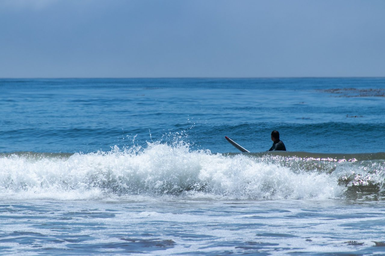 Surfer In Water Visible Behind Waves