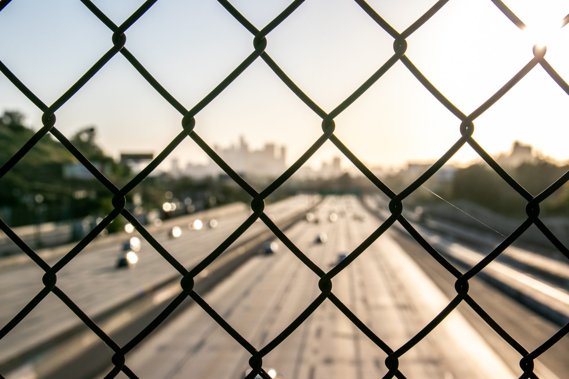Blurry Traffic Through Chain Link Fence