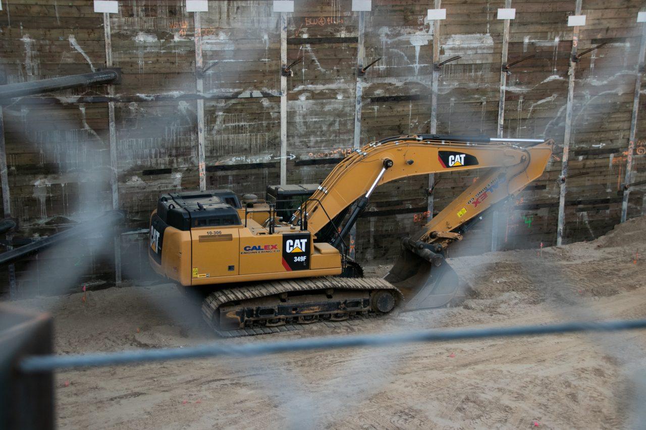 Excavator Through Blurry Chain Link Fence