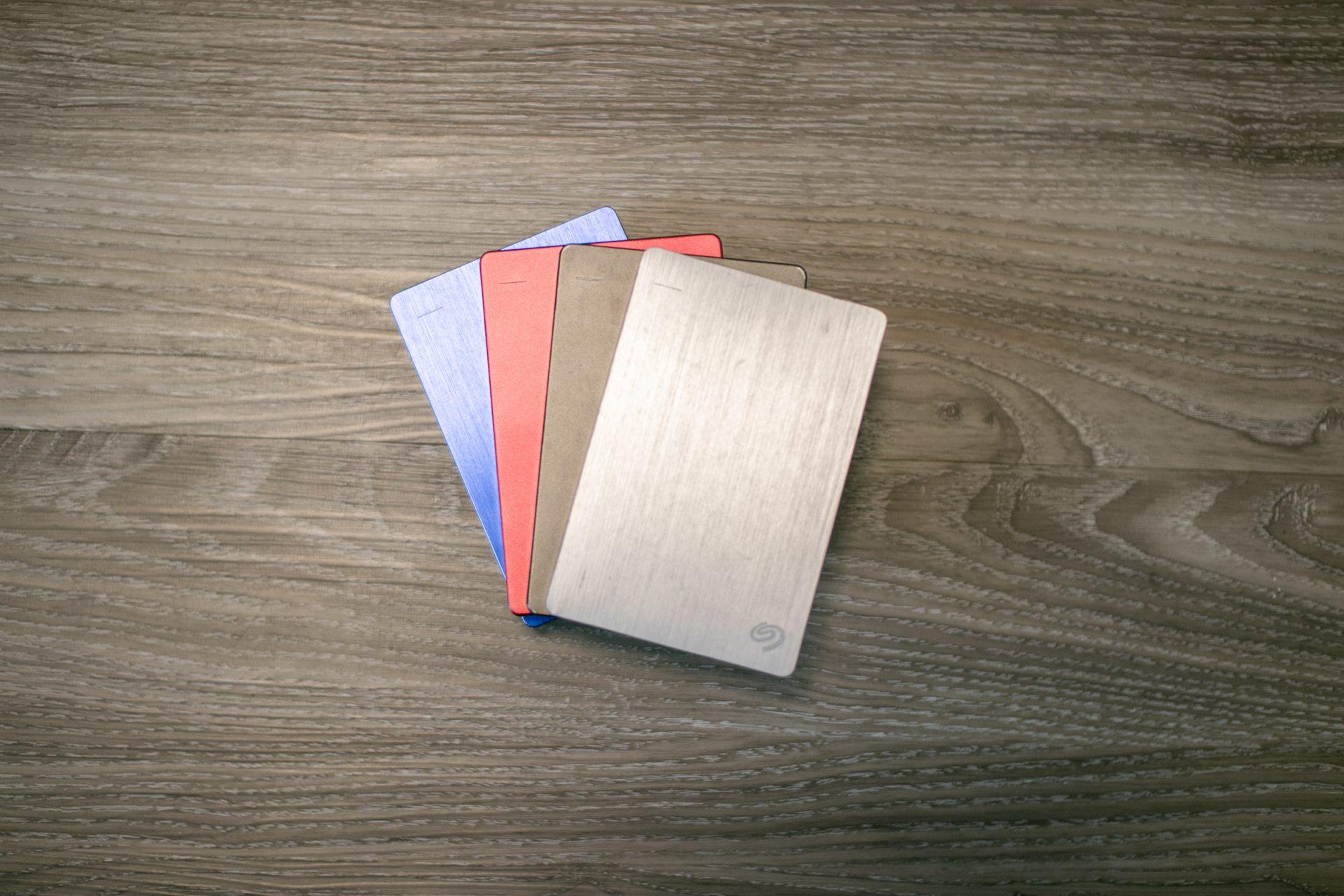 Four External Hard Disks On Wooden Surface