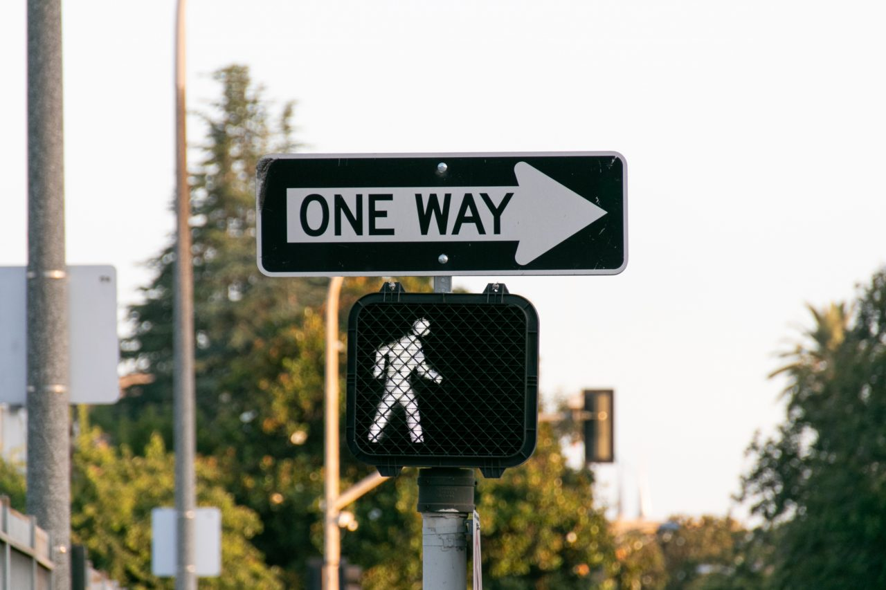 One Way And Crosswalk Signs Against Trees