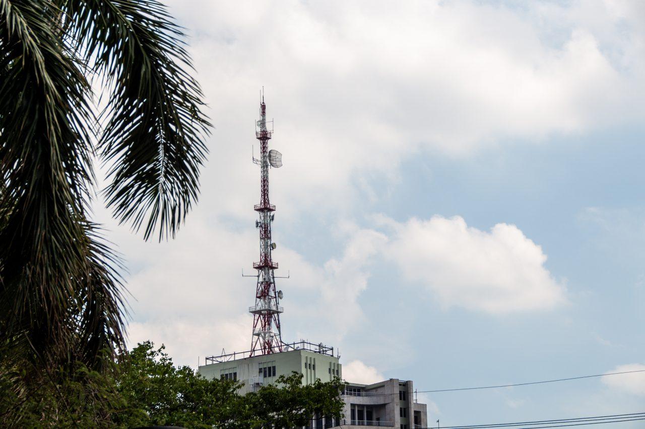 Radio Tower Atop Building Near Trees