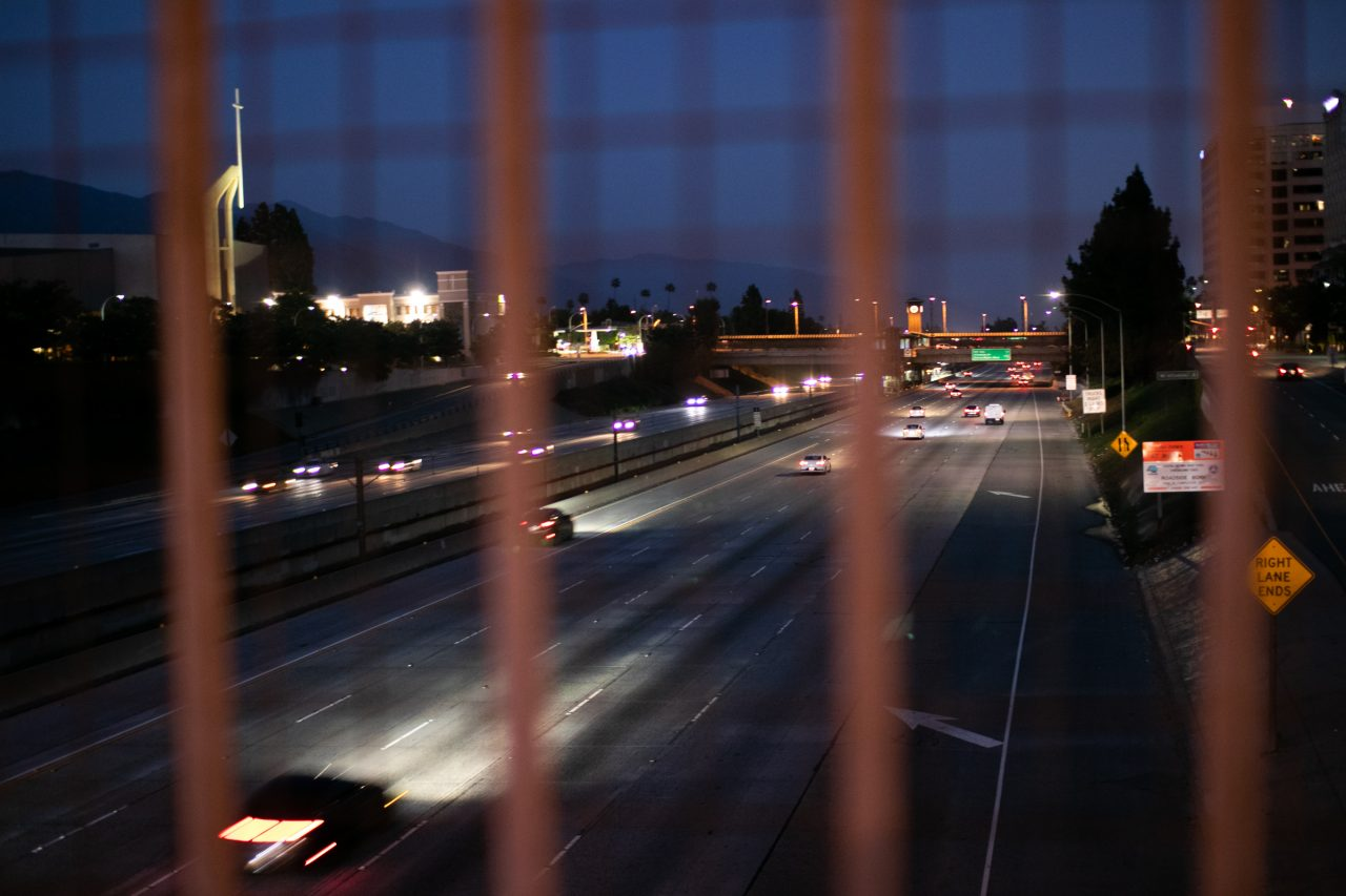 Traffic Through Blurry Wire Mesh Fence At Night