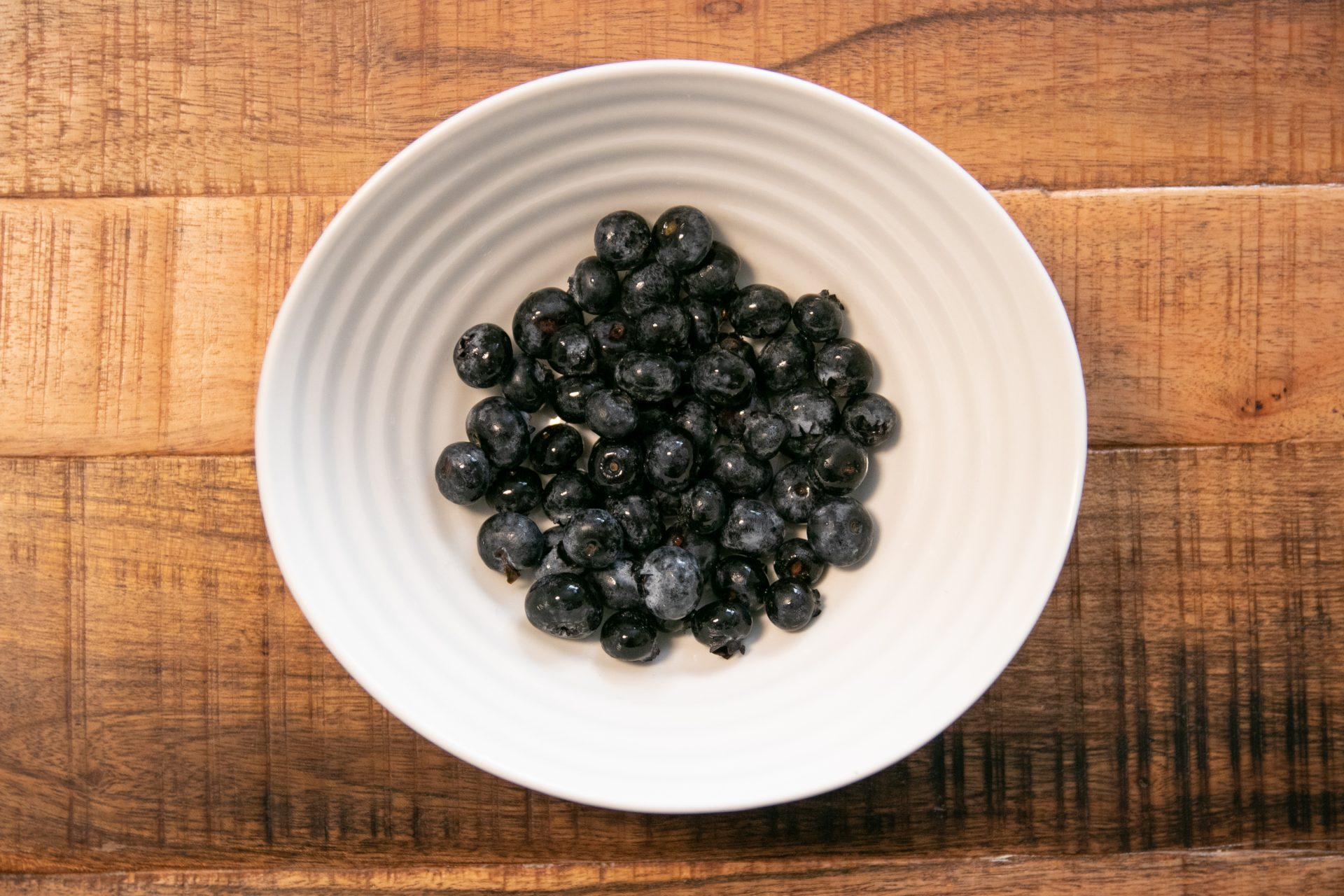 White Bowl Of Blueberries On Wooden Surface