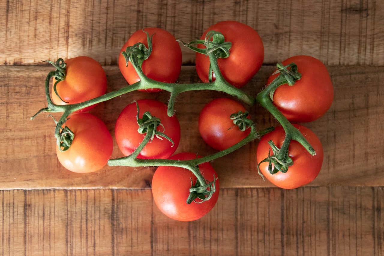 Linked Red Tomatoes On Wood