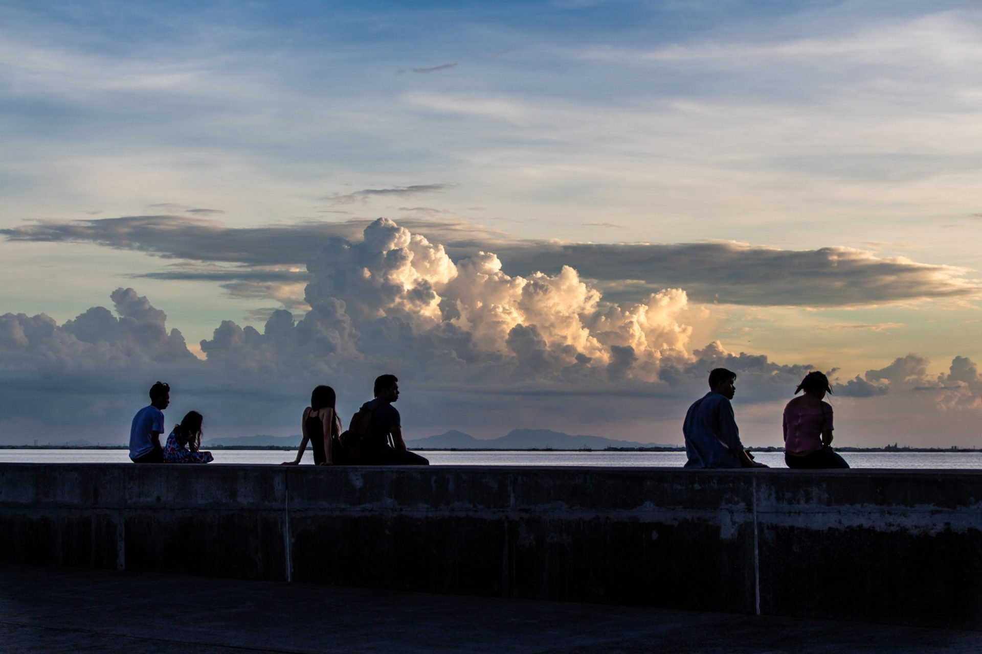 People Sitting On Coastal Ledge During Sunset
