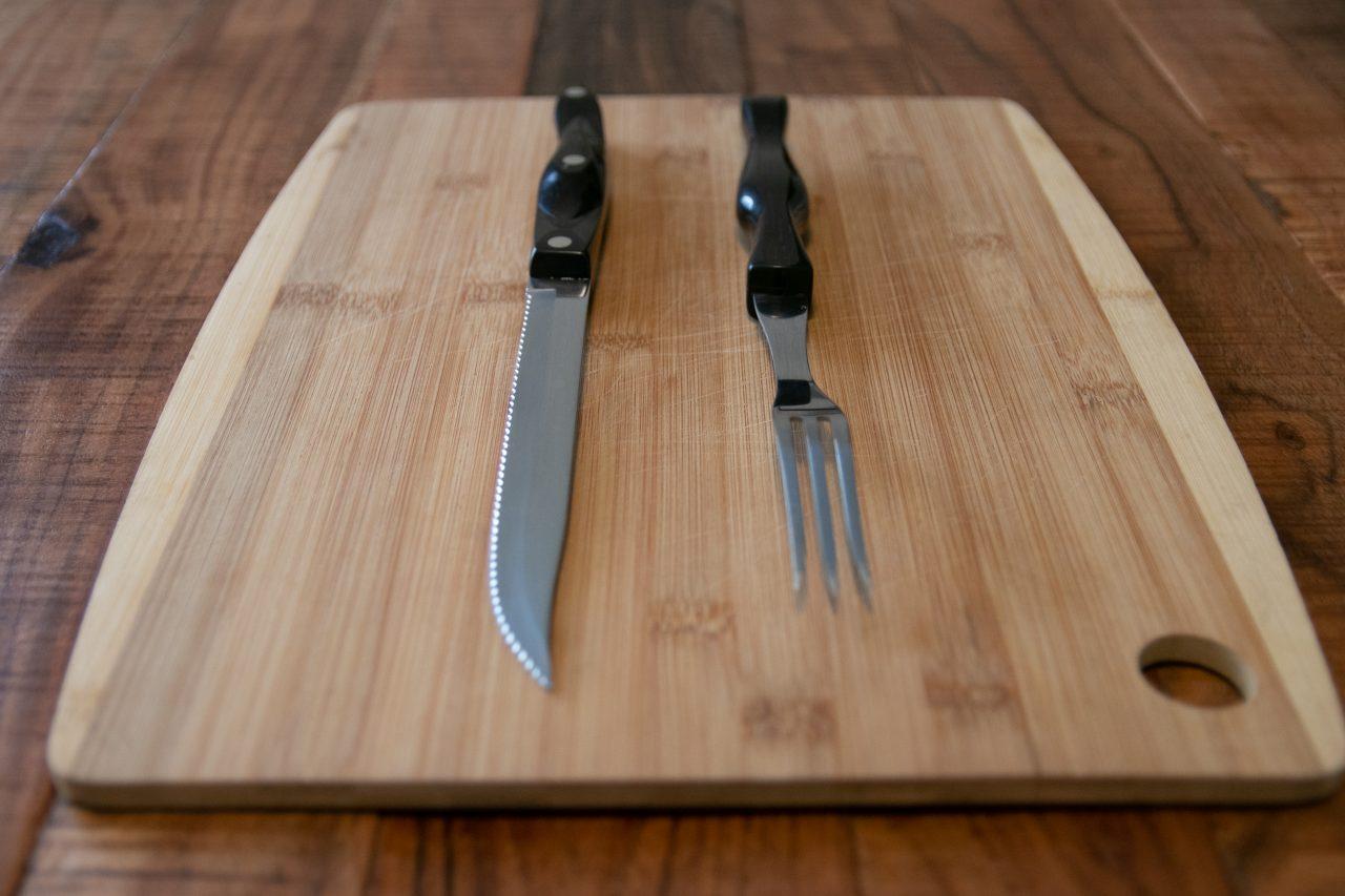 Steak Knife And Fork On Wood Chopping Board