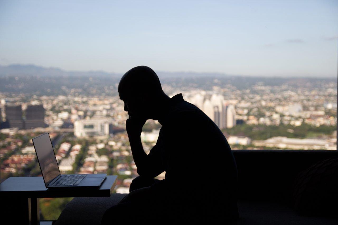 Man Sitting In Front Of Laptop Near Window