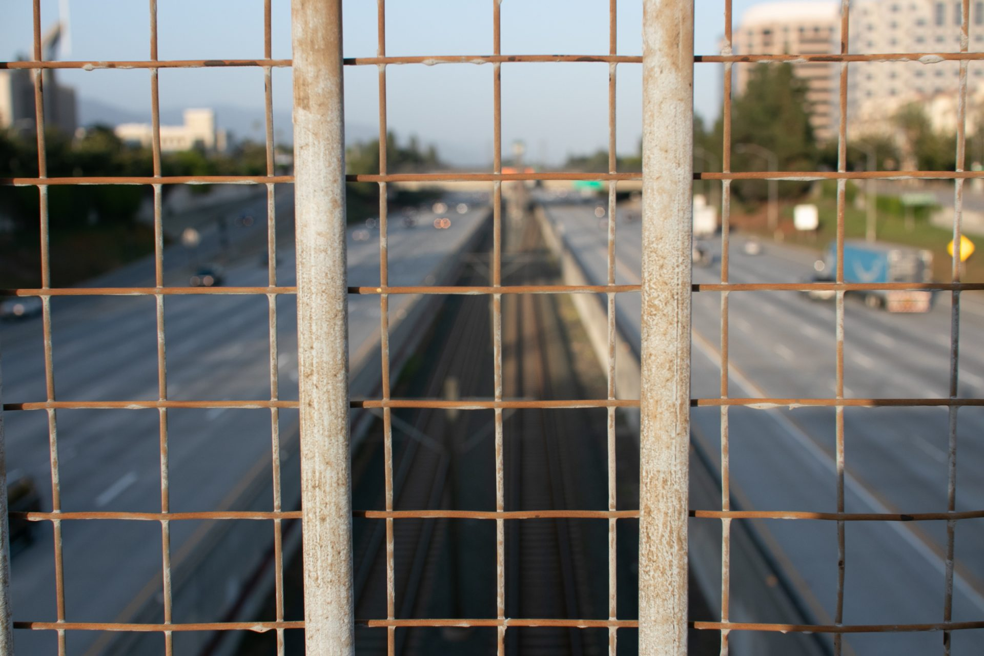 Blurry Divided Highway Beyond Wire Mesh Fence