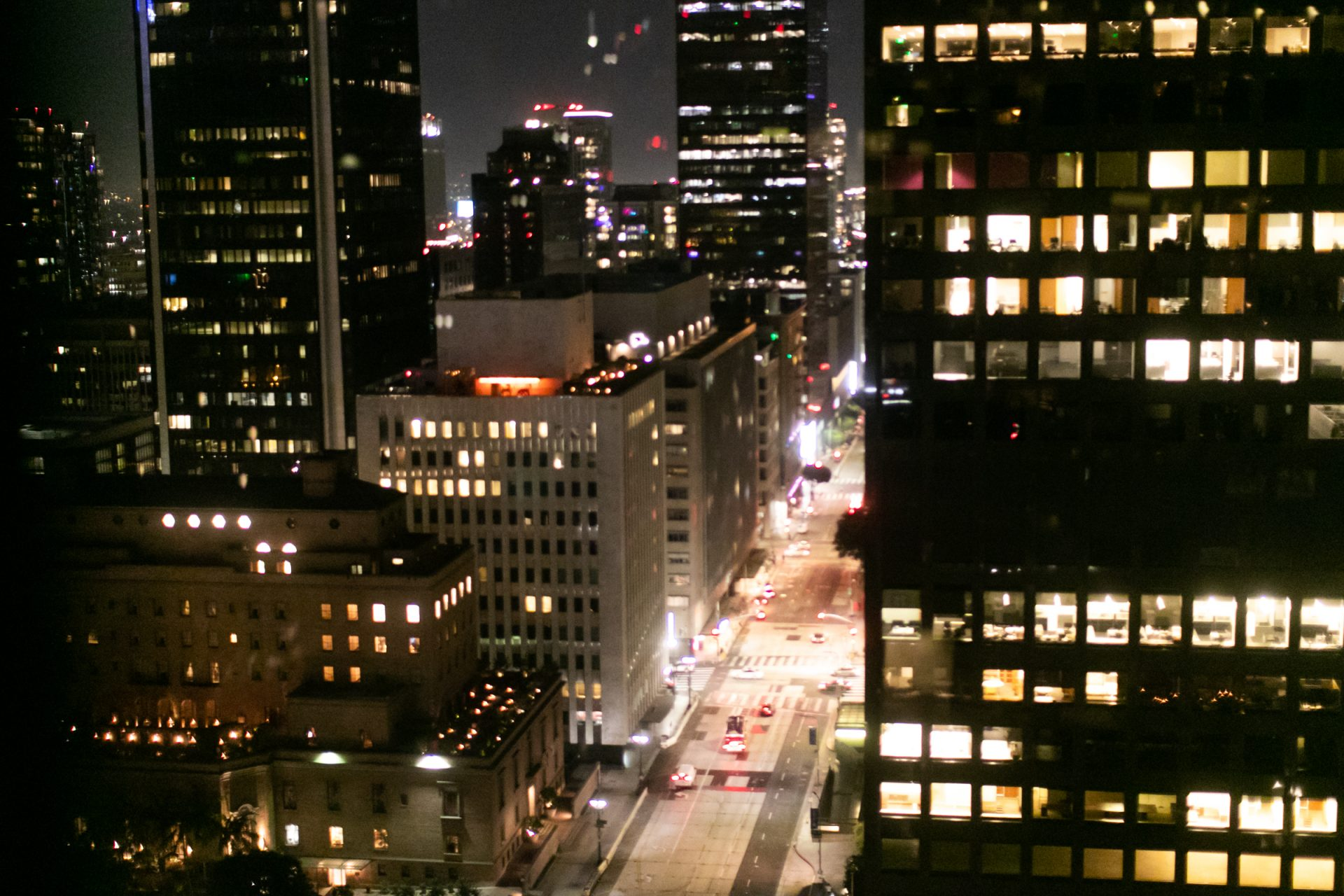 Brightly Illuminated Street Between Tall Buildings At Night
