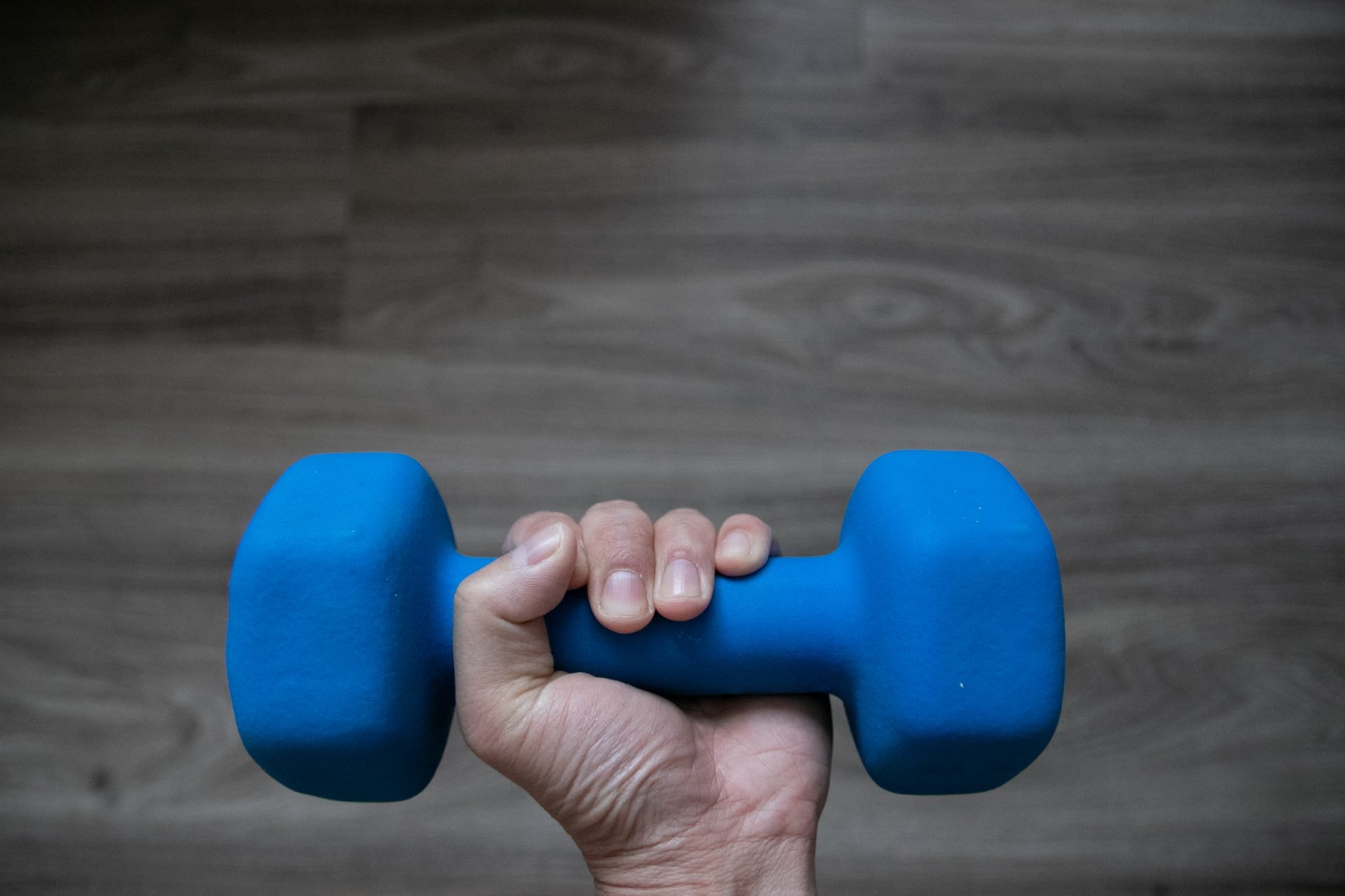 Left Hand Holding Blue Dumbbell