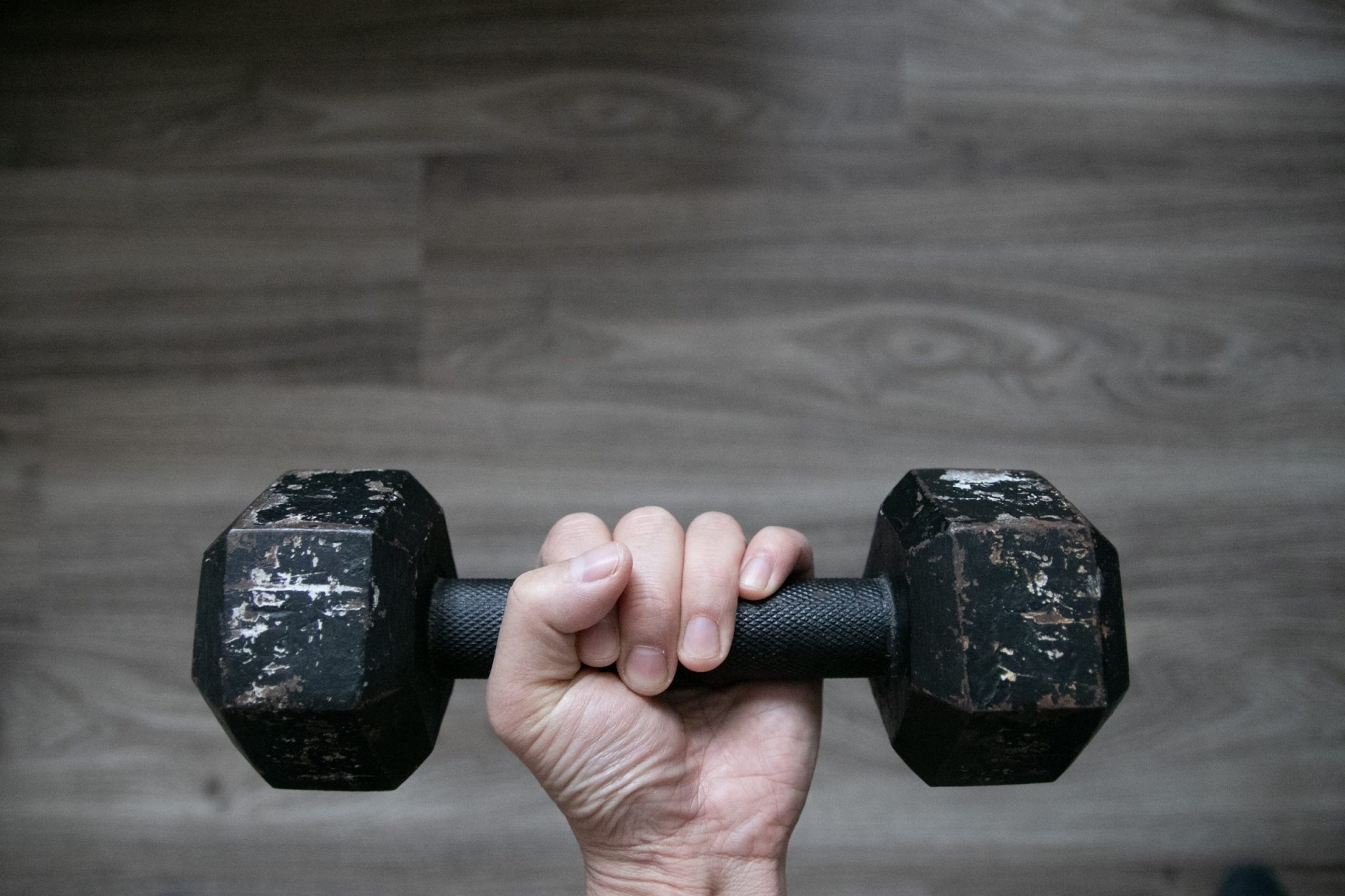 Left Hand Holding Scuffed Up Dumbbell