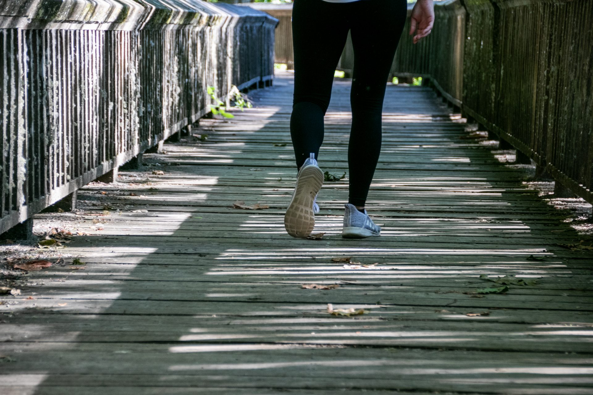 Legs Walking On Wooden Boardwalk