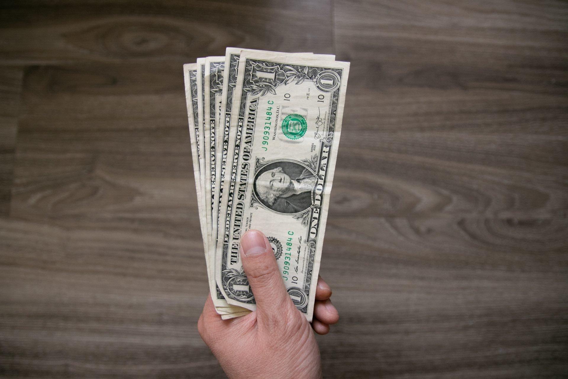 One Us Dollar Bills In Left Hand