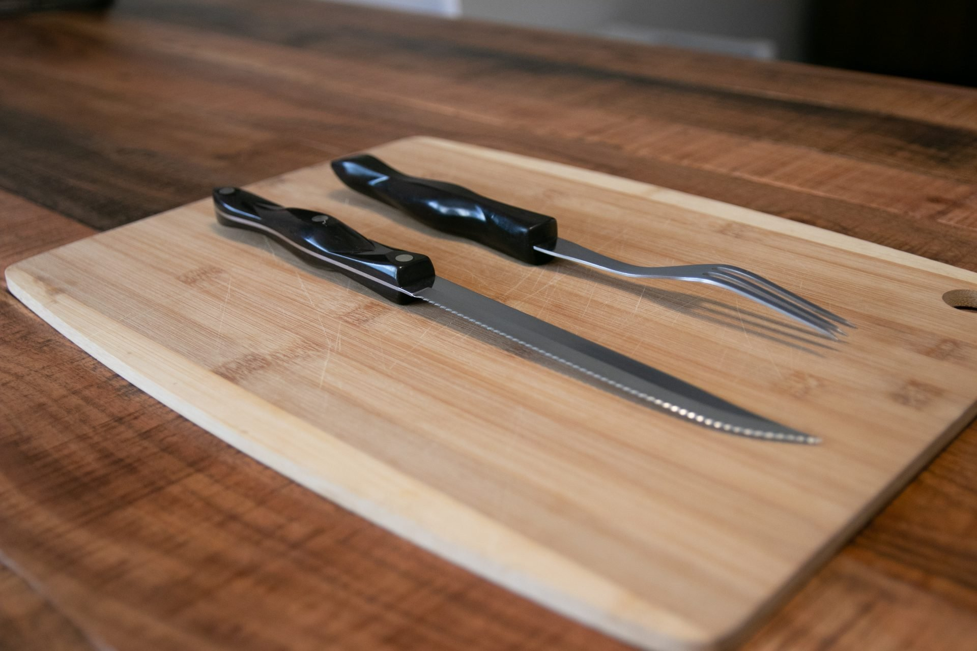 Steak Knife And Fork On Cutting Board